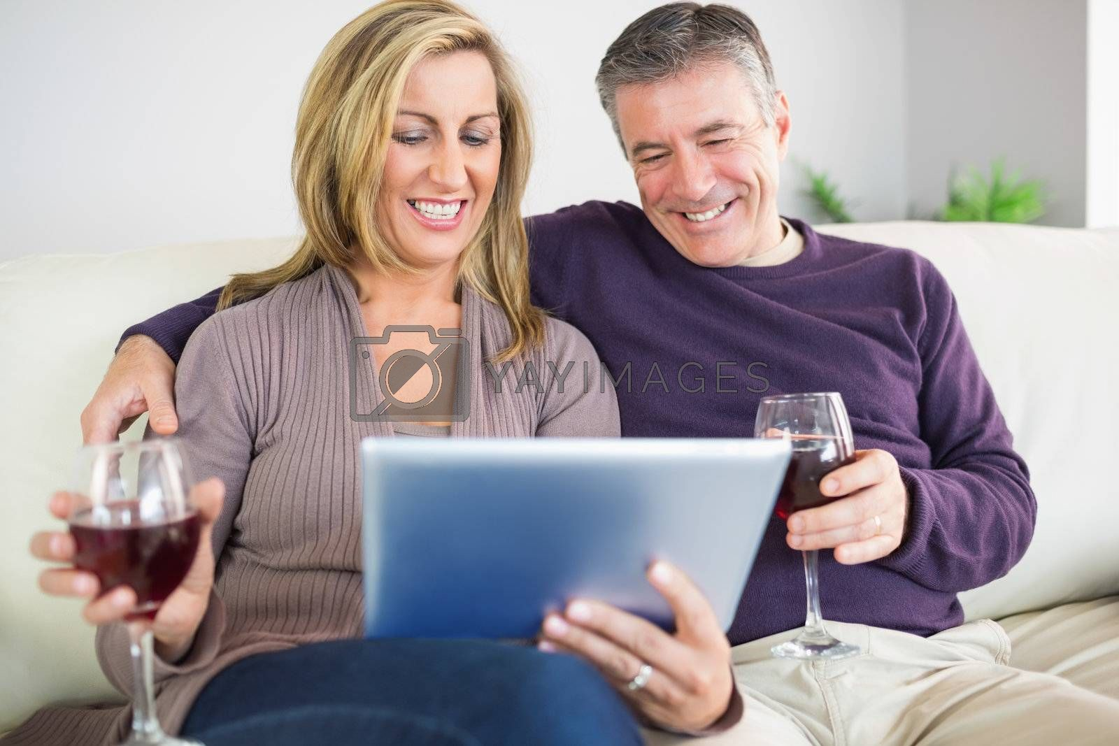 Happy couple watching their tablet pc and drinking wine by Wavebreakmedia