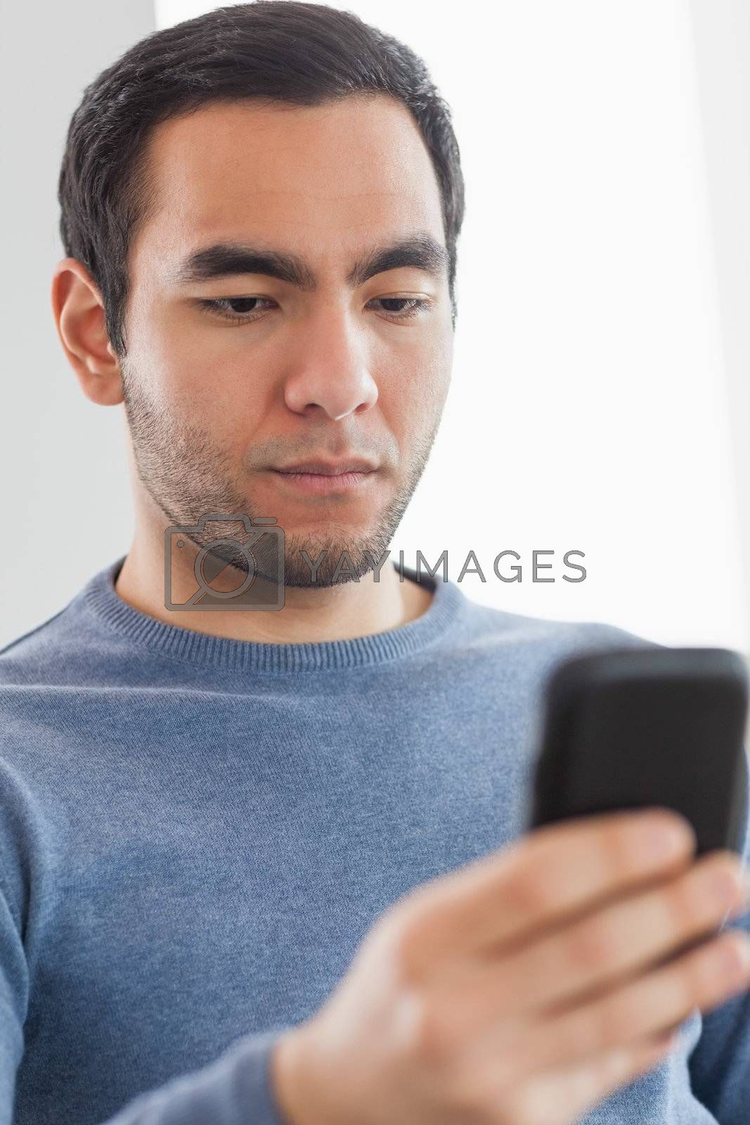 Serious casual man text messaging by Wavebreakmedia