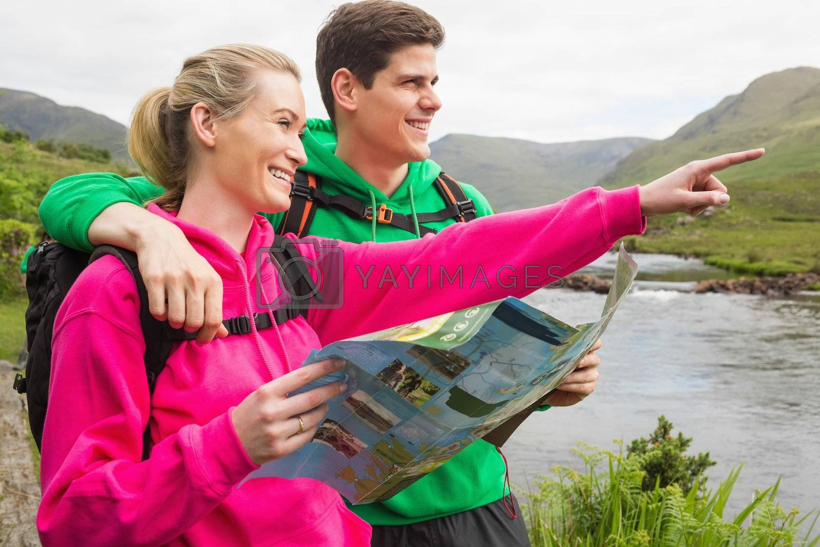 Athletic couple in hooded jumpers on a hike holding map by Wavebreakmedia