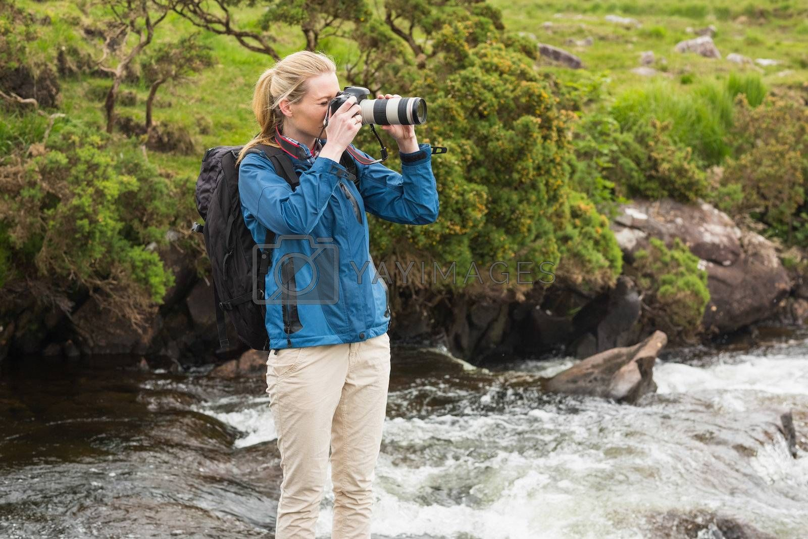 Blonde standing on rock in a stream taking a photo by Wavebreakmedia