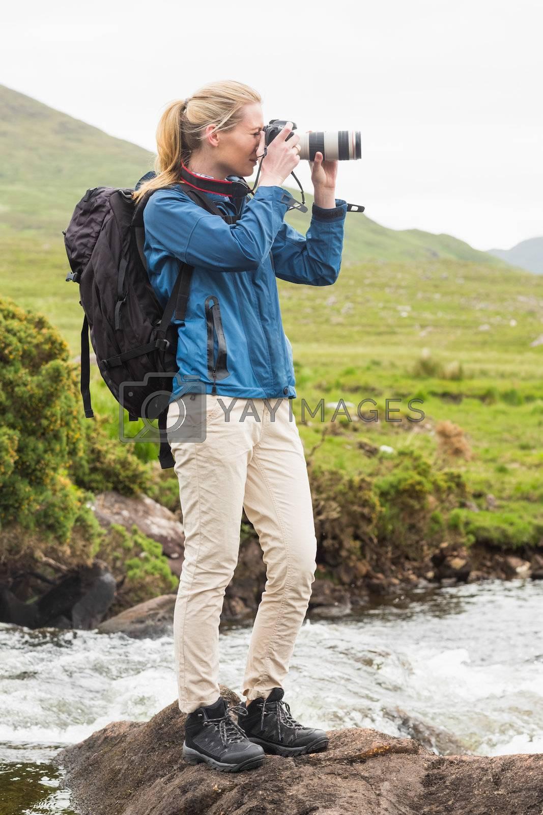 Blonde woman on a hike taking a photo by Wavebreakmedia