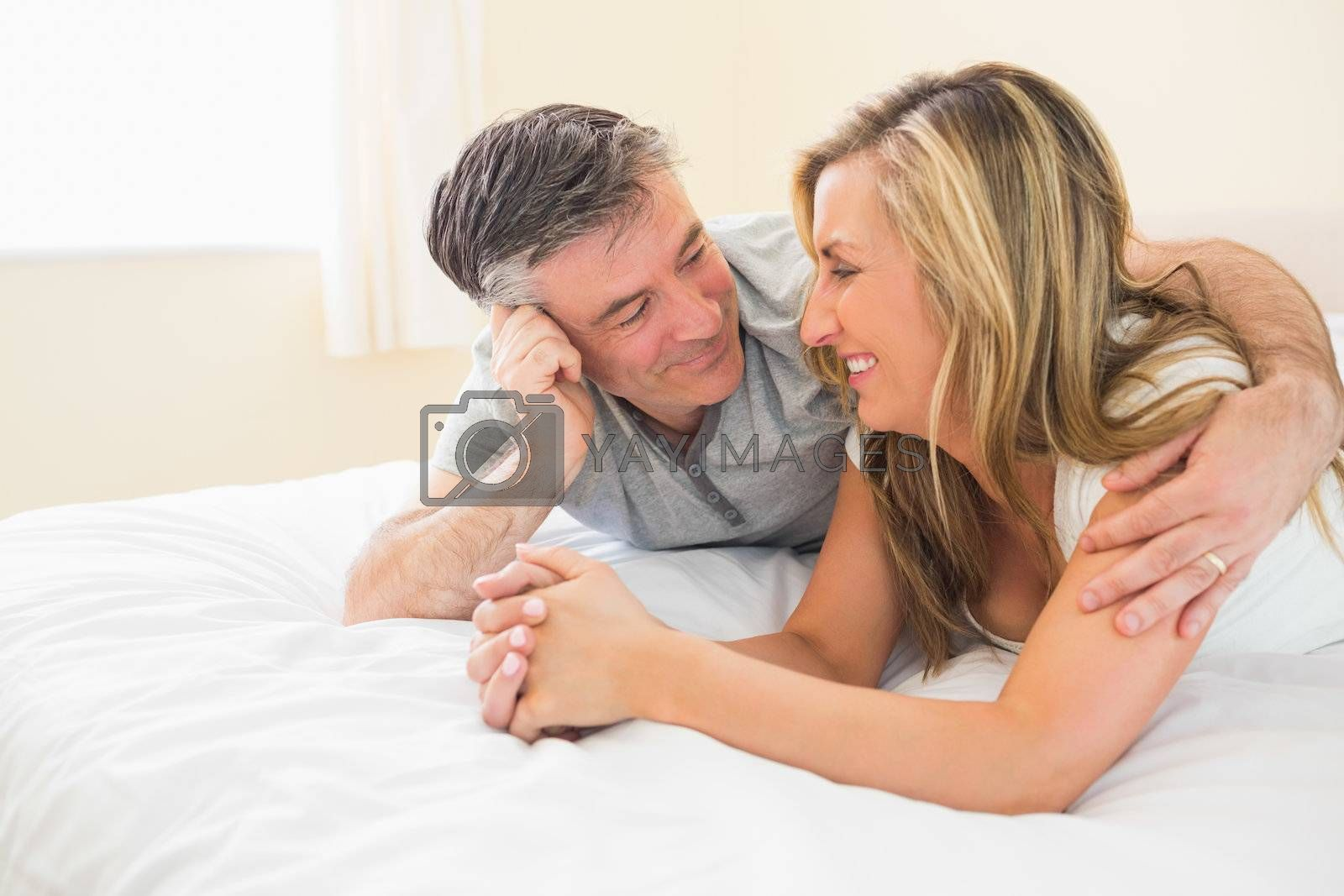Happy couple lying on a bed and looking each other by Wavebreakmedia