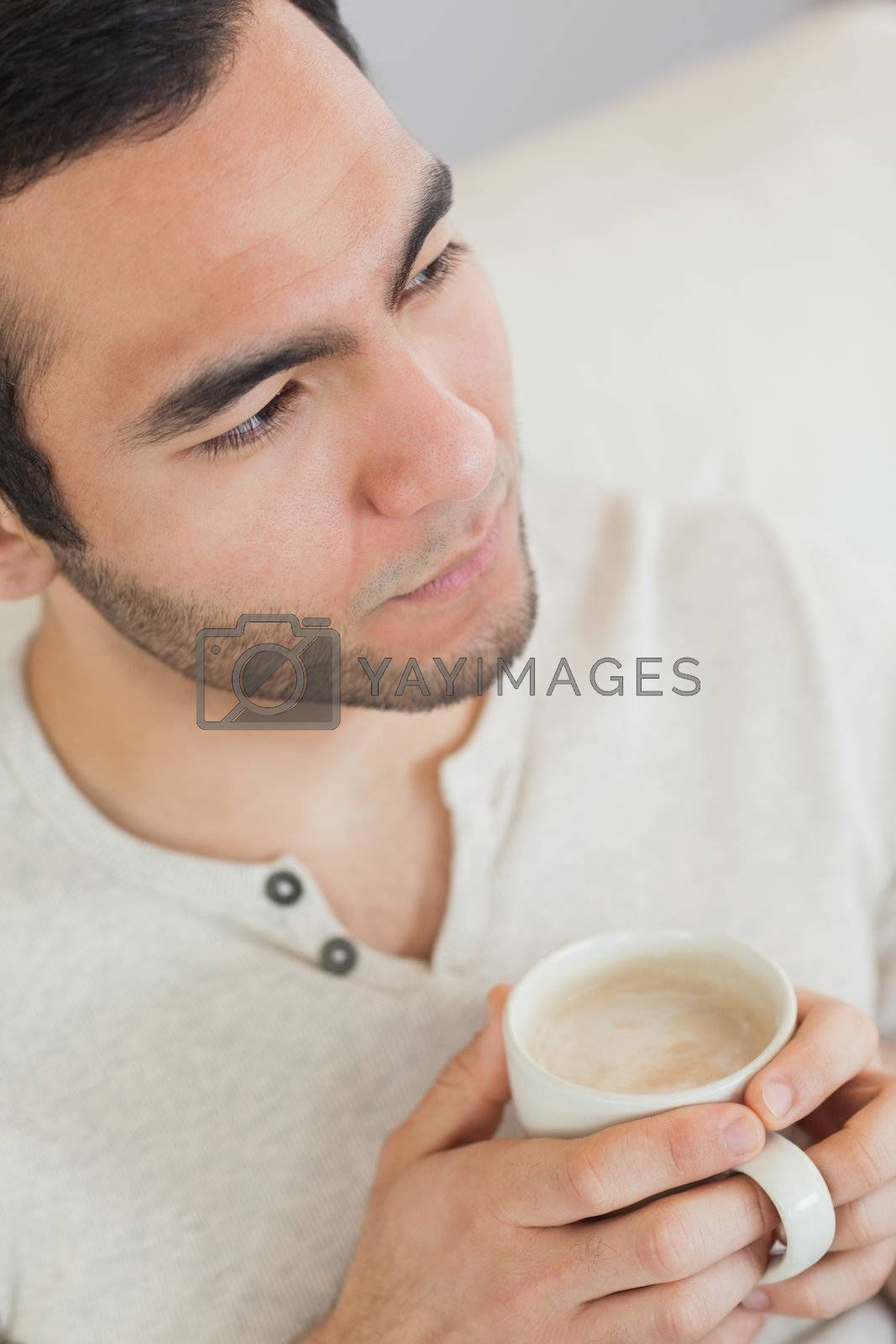 Thoughtful handsome man holding cup of coffee by Wavebreakmedia