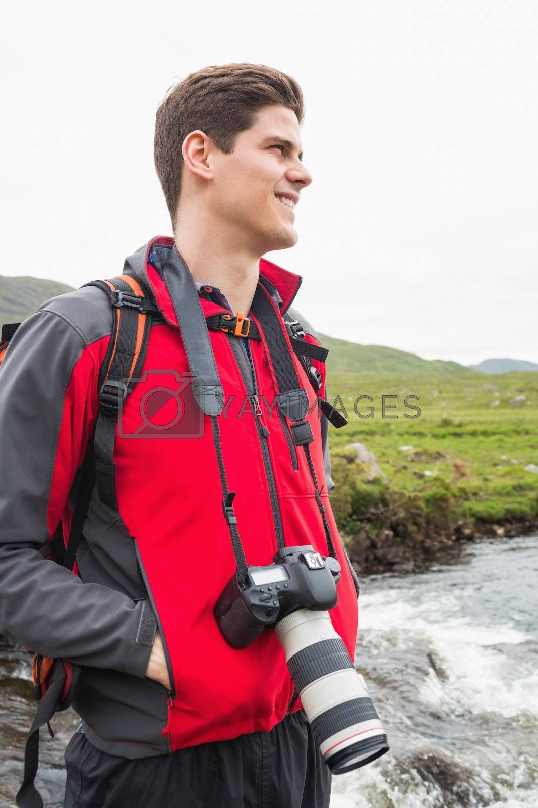 Brunette man on hike withcamera around his neck by Wavebreakmedia