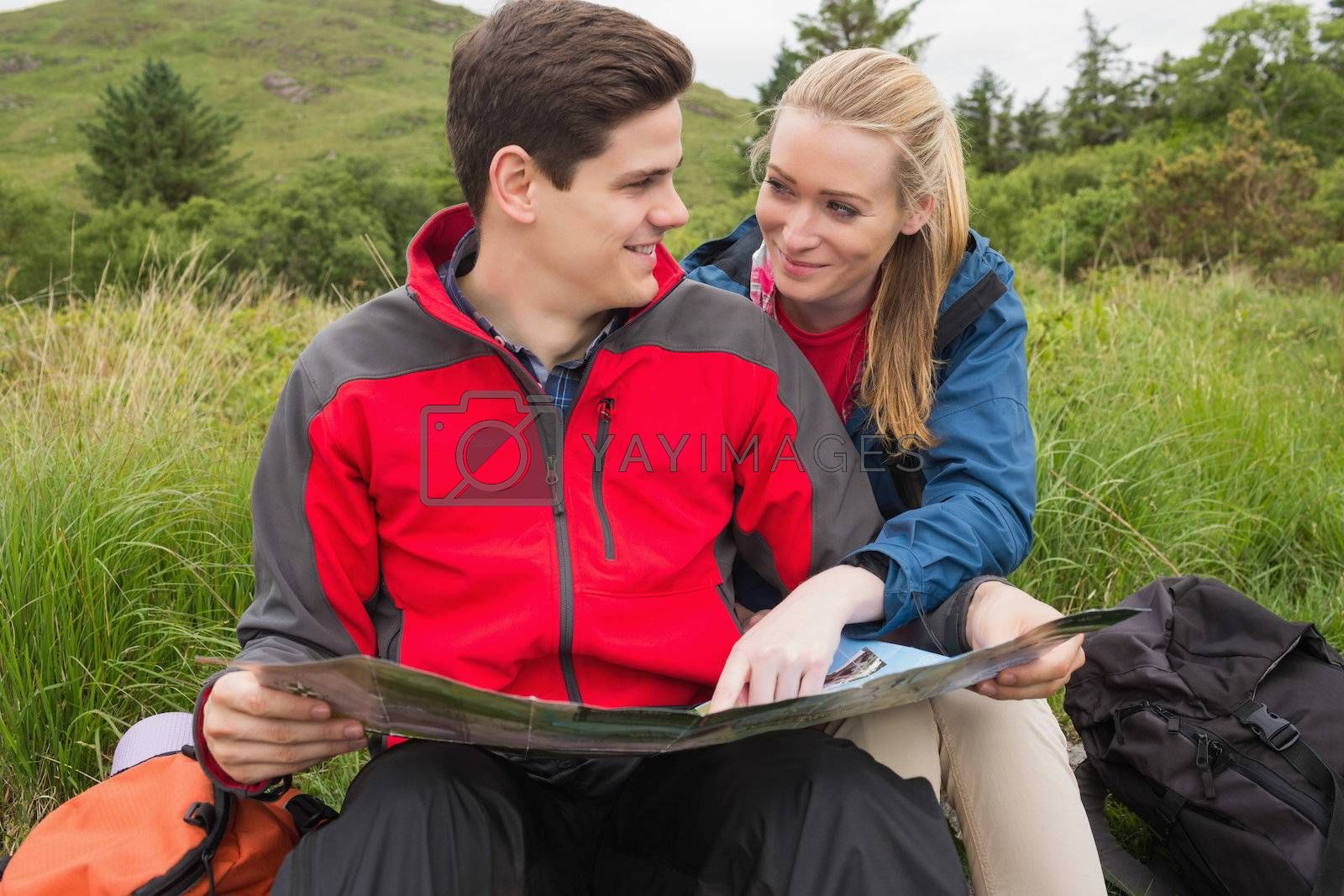 Smiling couple taking a break on hike to look at map by Wavebreakmedia
