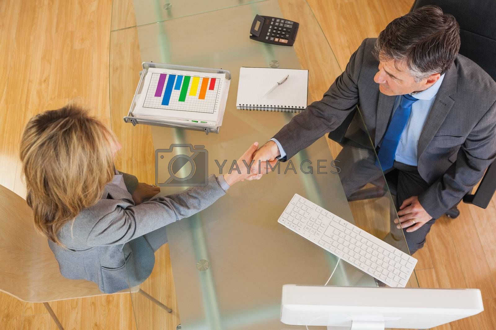 Two business people having a handshake above a desk by Wavebreakmedia