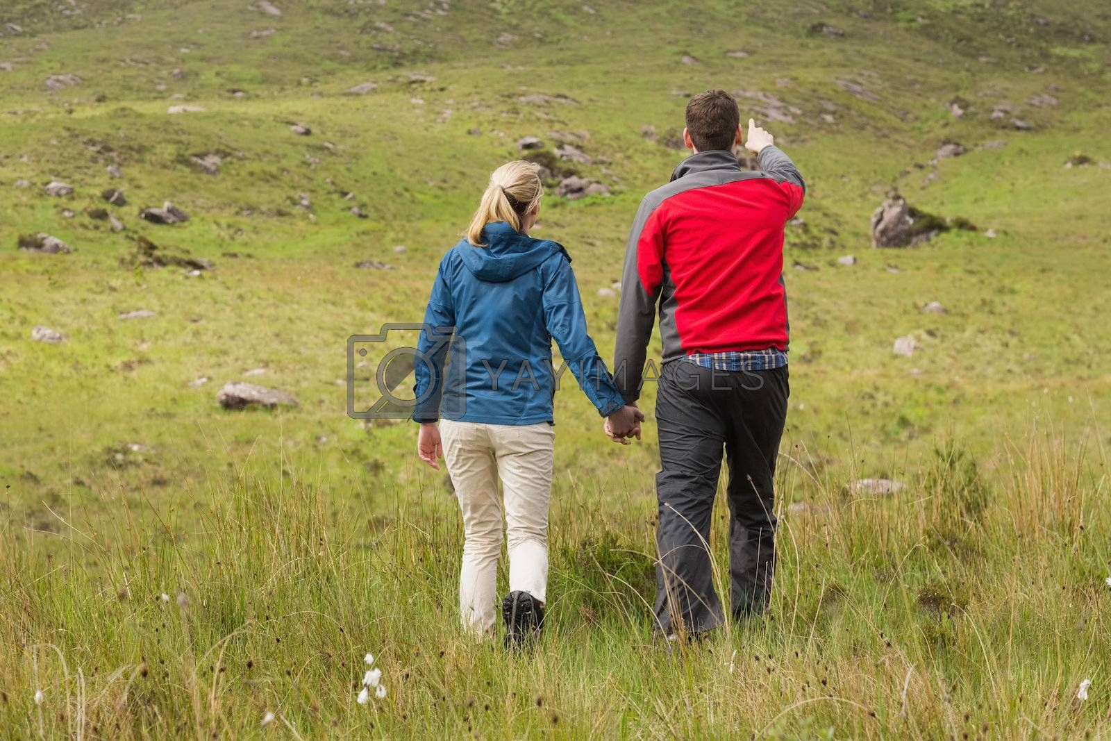 Couple holding hands on walk with man pointing by Wavebreakmedia