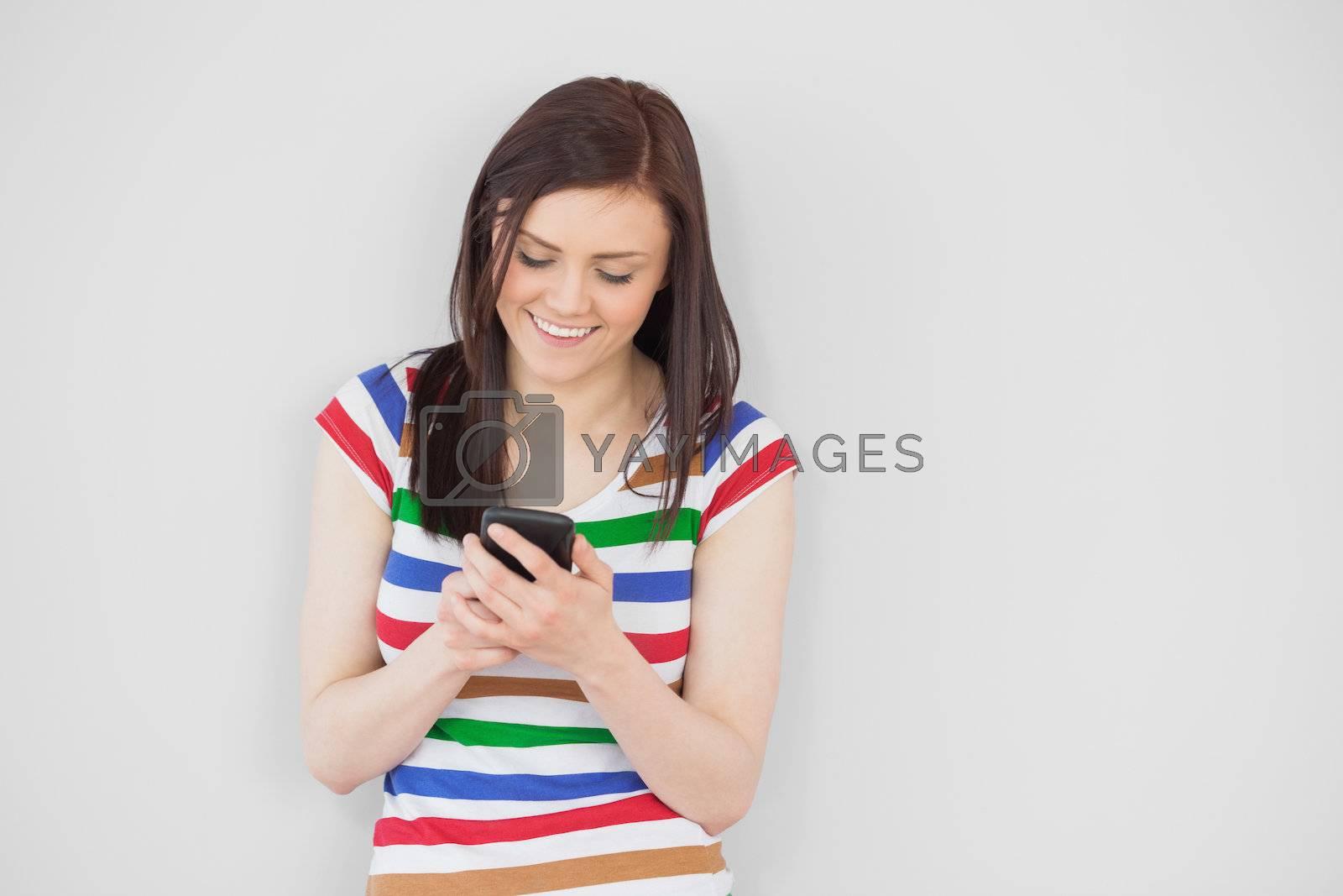 Smiling girl using her mobile phone by Wavebreakmedia