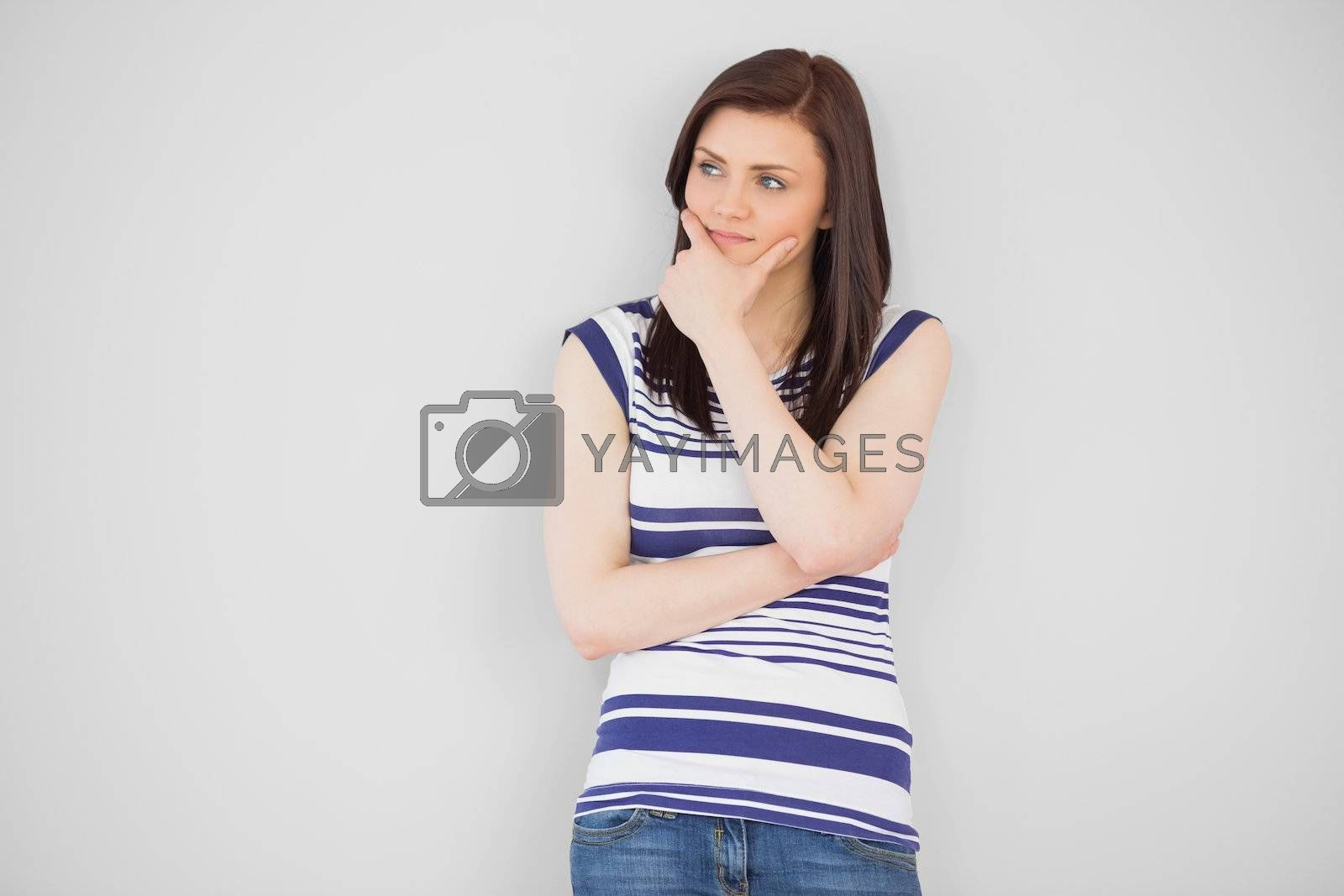 Thinking girl standing and looking away by Wavebreakmedia