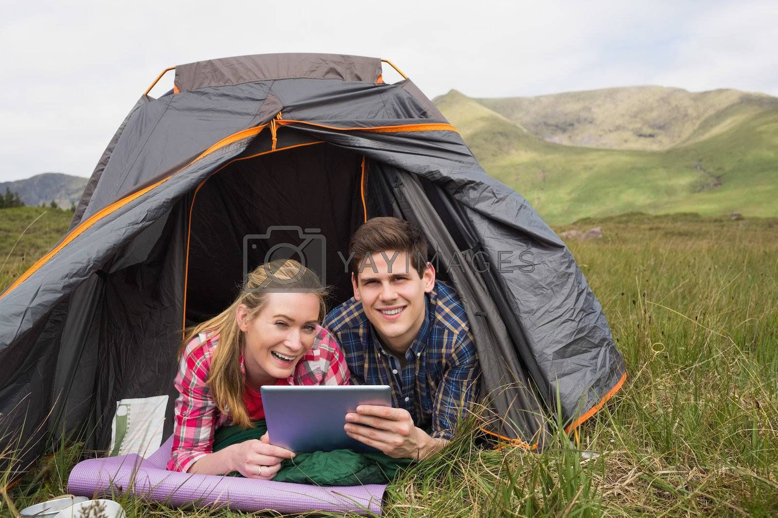 Smiling couple lying in their tent and using digital tablet by Wavebreakmedia