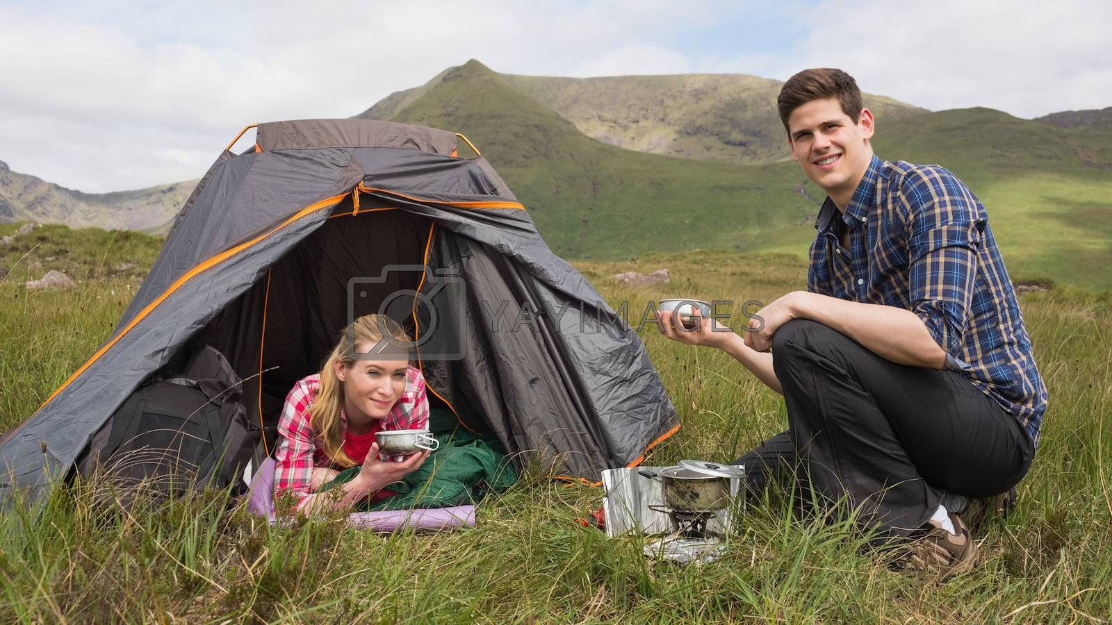 Smiling couple cooking outdoors on camping trip by Wavebreakmedia