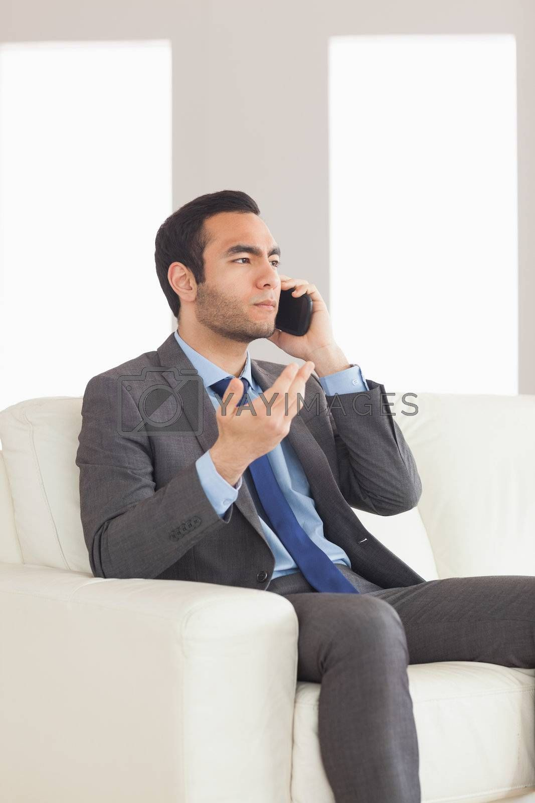 Serious businessman having a phone call sitting on cosy sofa by Wavebreakmedia