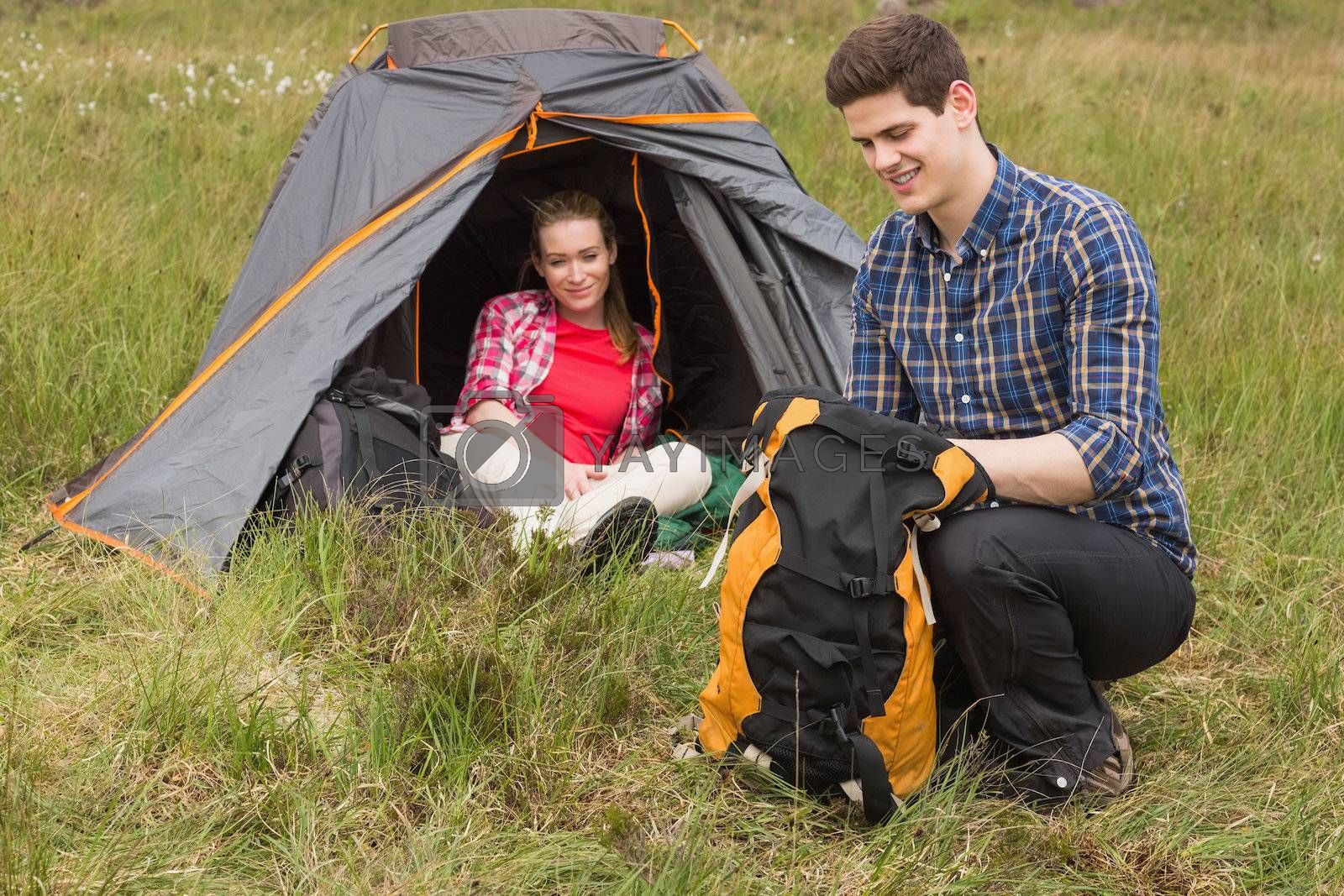Happy man packing backpack while girlfriend sits in tent by Wavebreakmedia