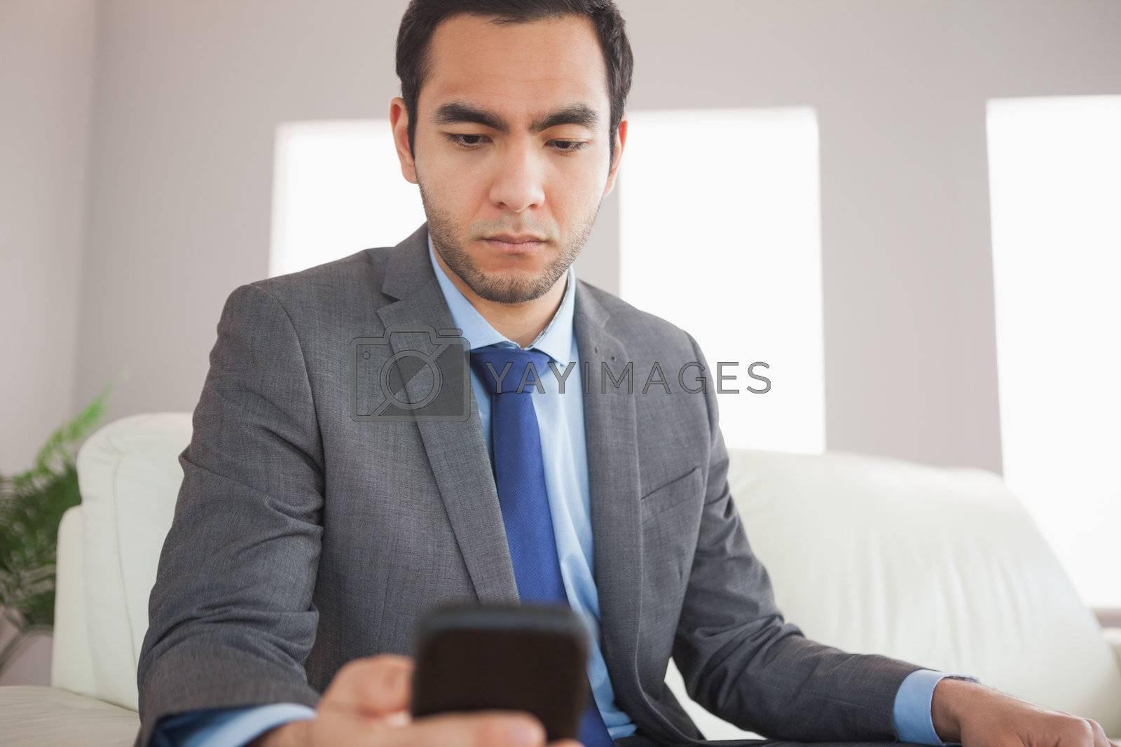Serious businessman sending a text message by Wavebreakmedia