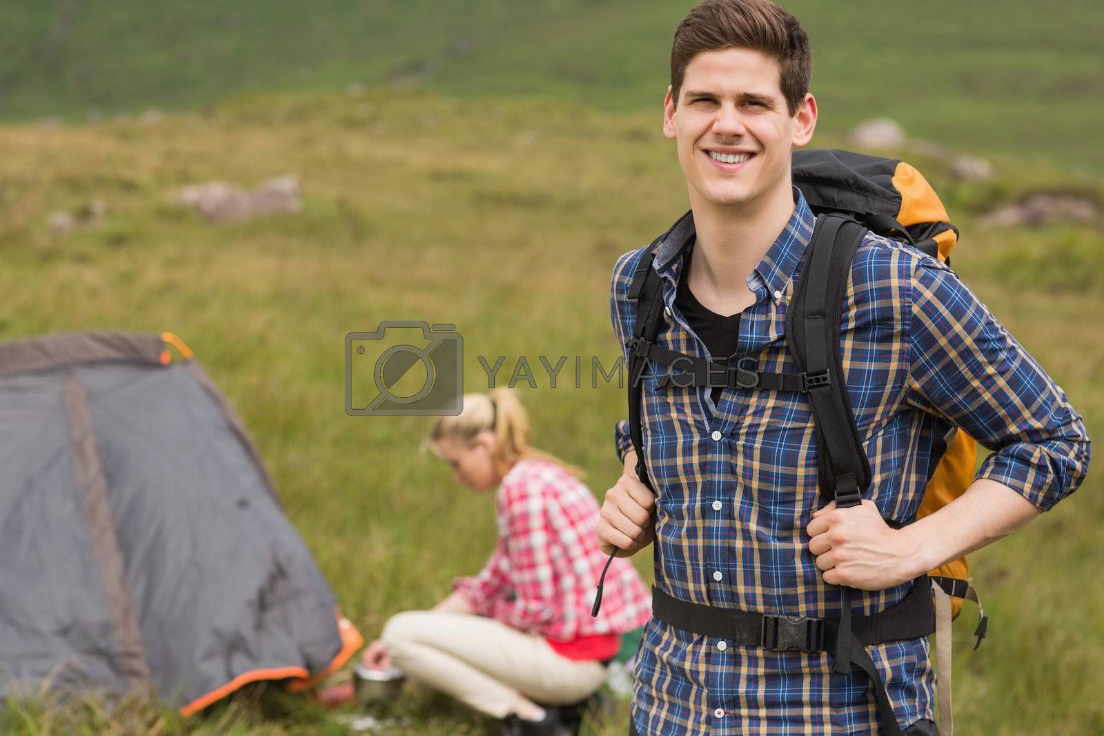 Cheerful man carrying backpack while girlfriend is pitching tent by Wavebreakmedia