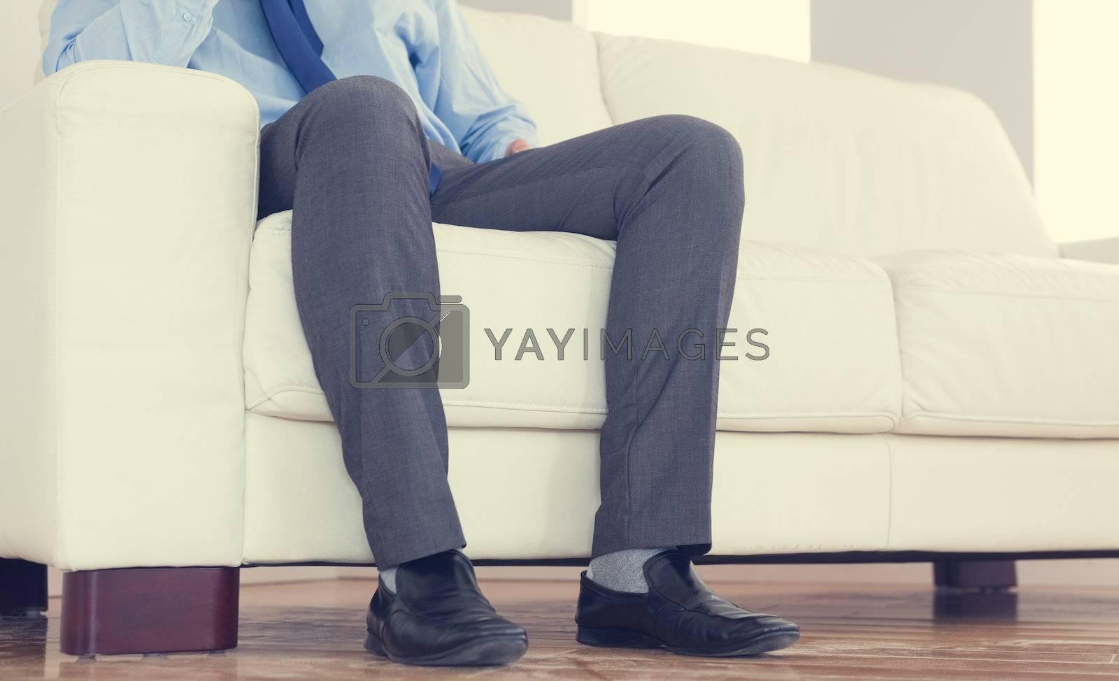 Low part of classy businessman sitting on cosy sofa by Wavebreakmedia