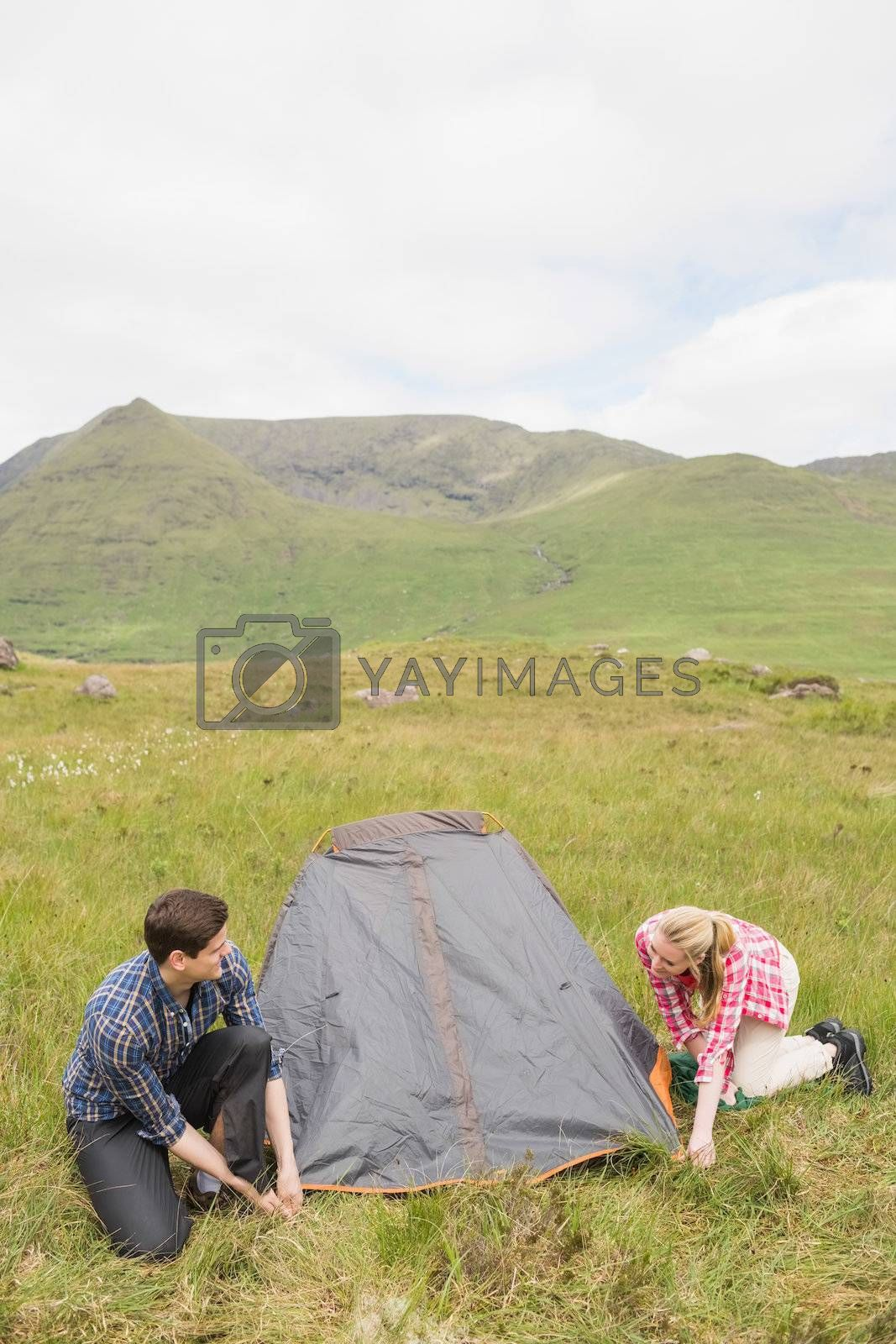 Smiling couple pitching their tent by Wavebreakmedia