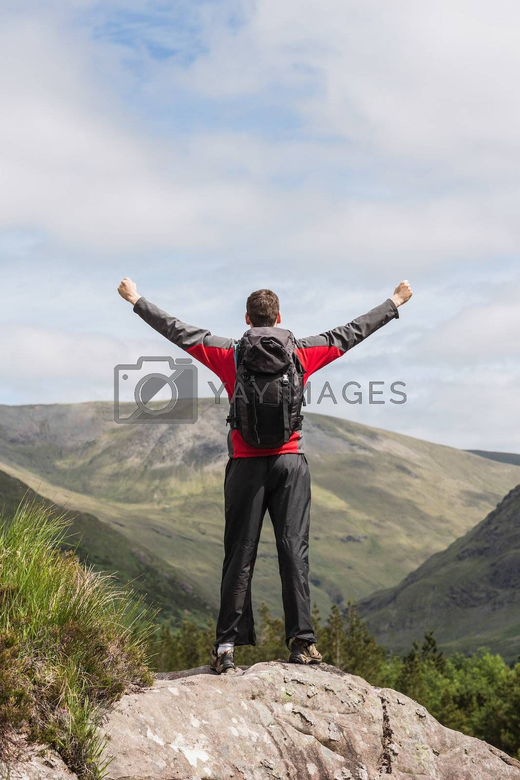 Man standing at hill top cheering by Wavebreakmedia