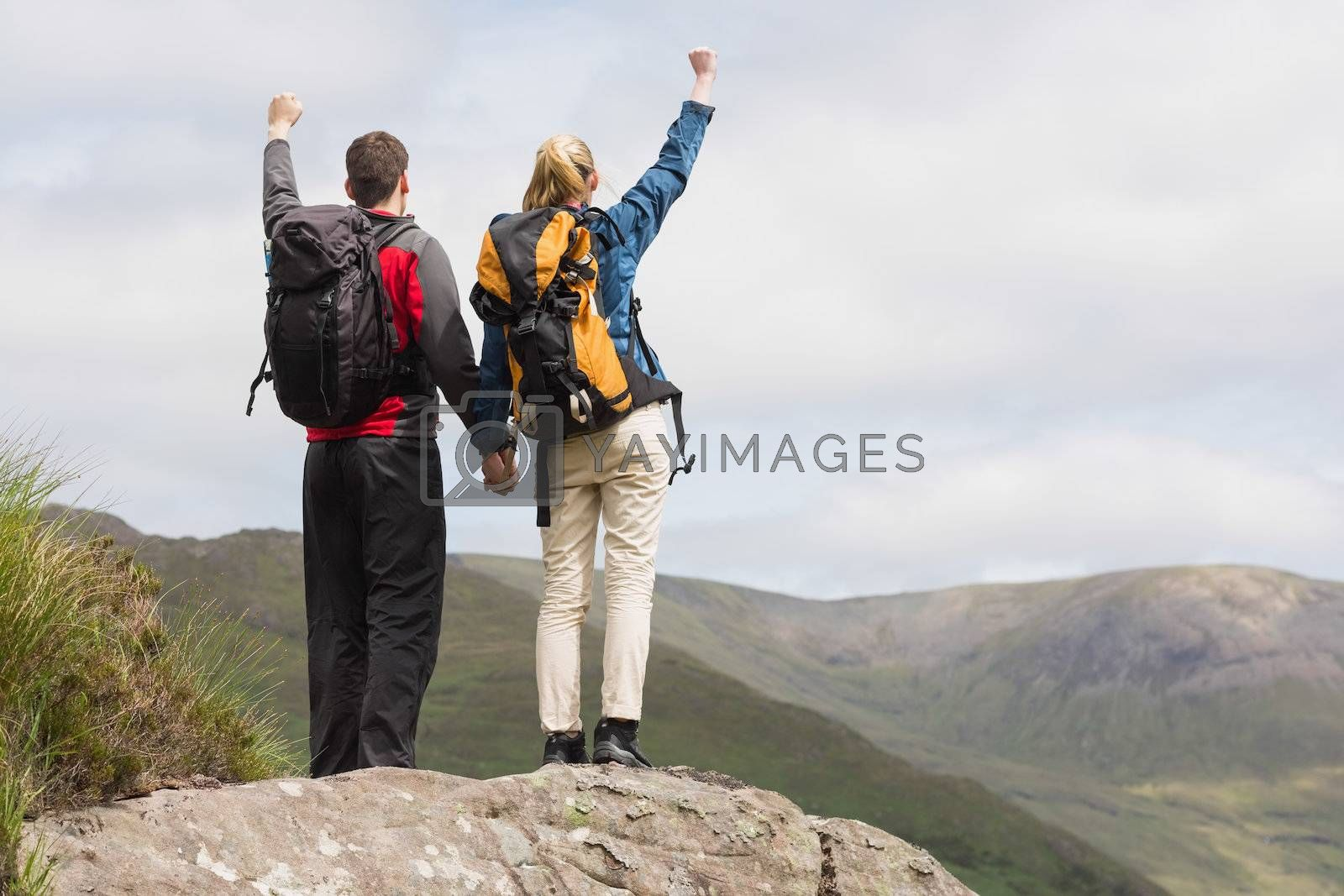 Excited couple reaching the top of their hike and cheering by Wavebreakmedia