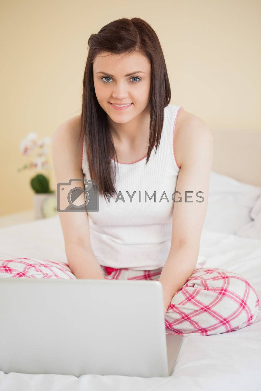 Smiling girl using a laptop sitting on her bed looking at camera by Wavebreakmedia