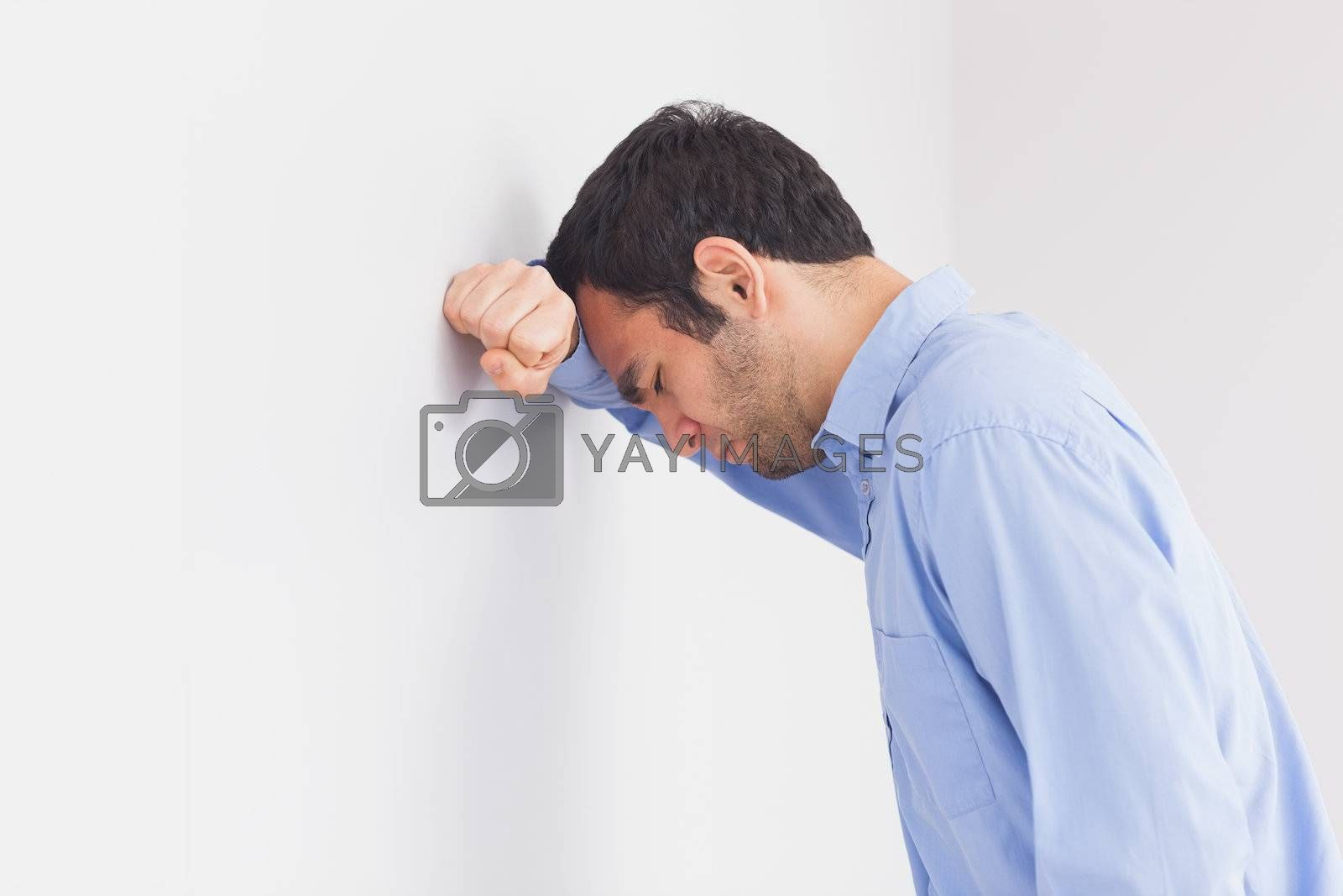 Upset man leaning his head against a wall by Wavebreakmedia