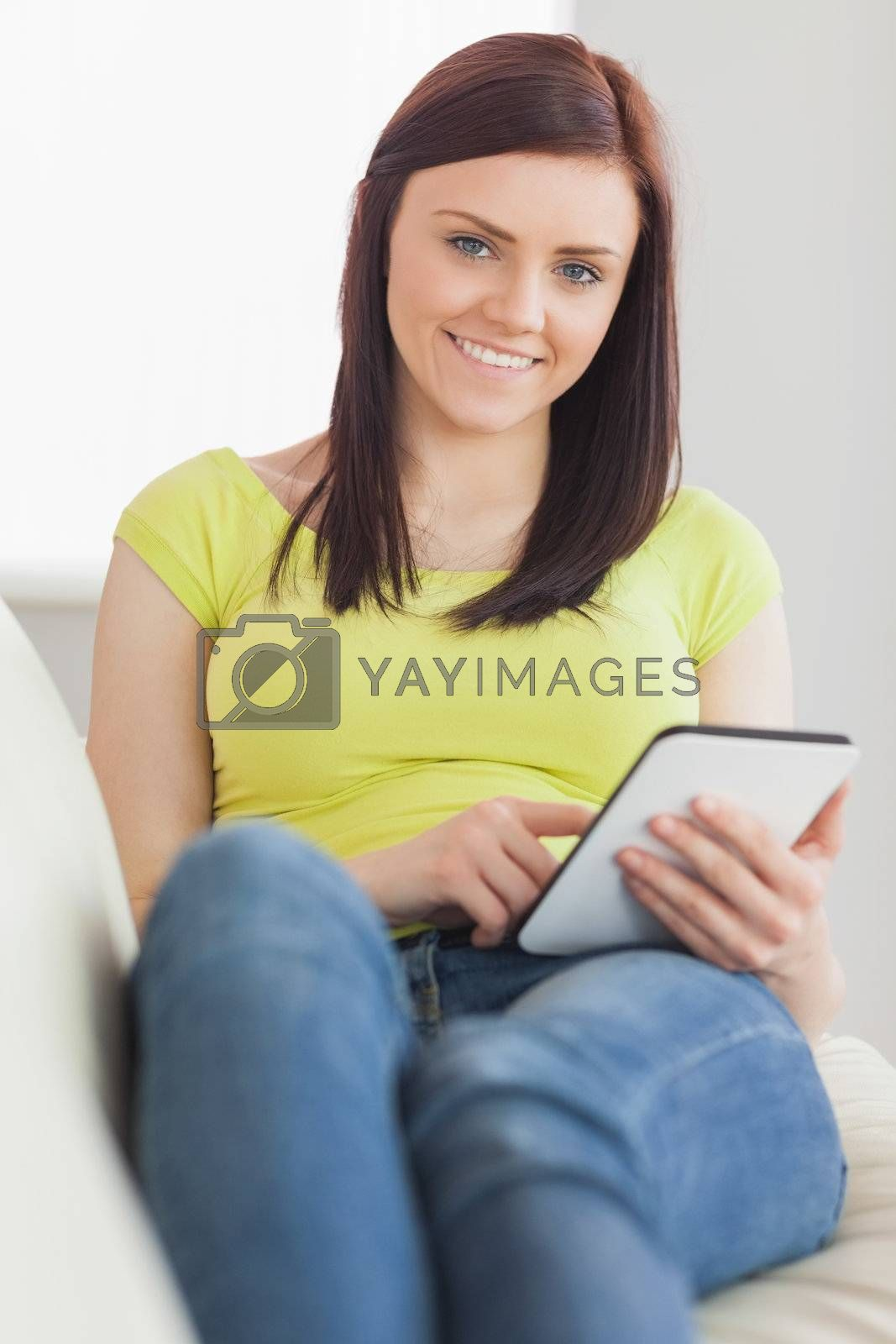 Relaxed girl sitting on a sofa using a tablet pc  by Wavebreakmedia