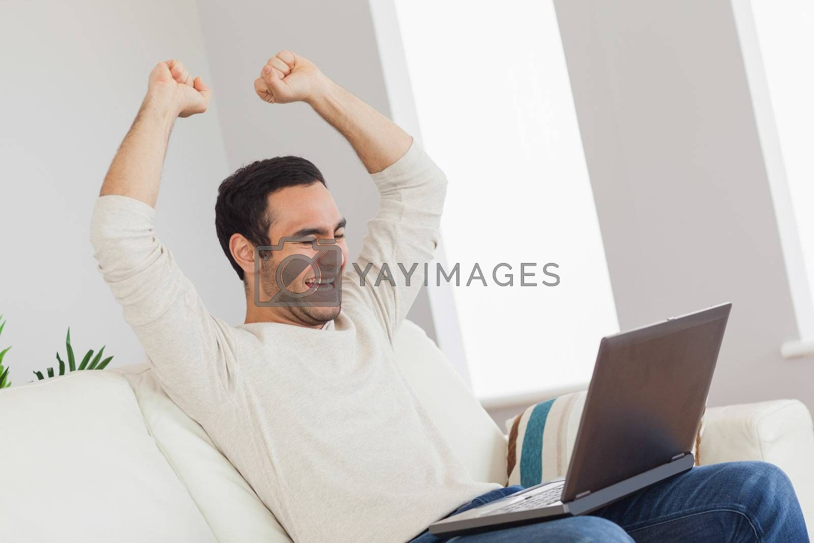 Victorious handsome man looking at his laptop by Wavebreakmedia