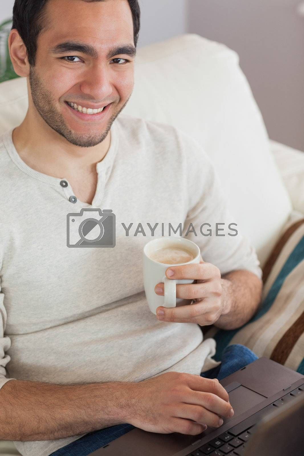 Smiling attractive man drinking coffee while using his laptop by Wavebreakmedia