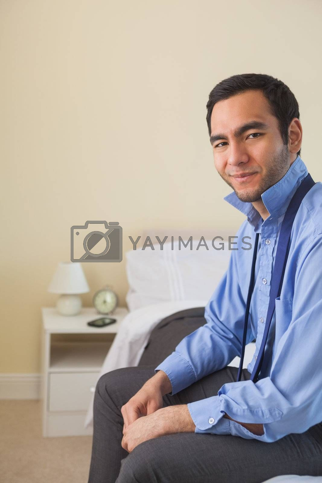 Satisfied man looking at camera and relaxing sitting on his bed by Wavebreakmedia