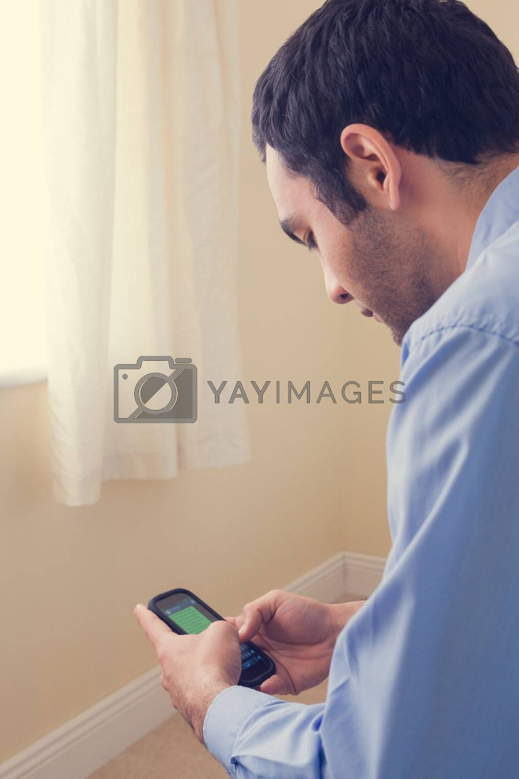 Close up of a man using a mobile phone sitting on a bed by Wavebreakmedia