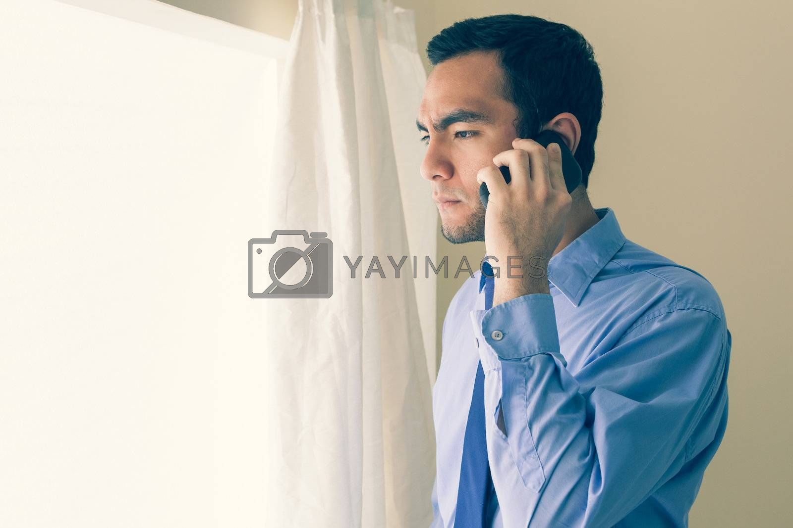 Irritated man calling someone with a mobile phone and looking out the window by Wavebreakmedia