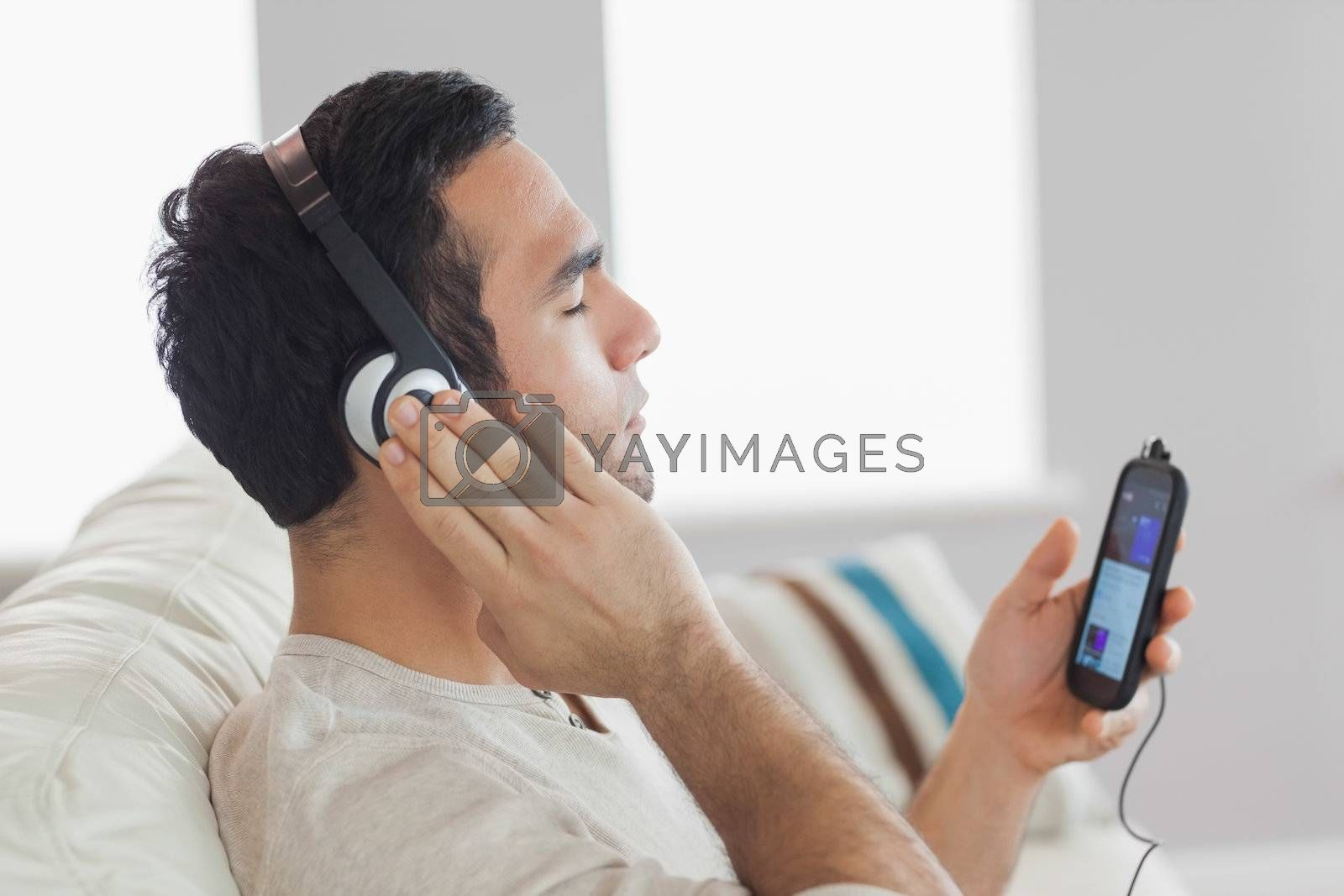Content handsome man listening to music by Wavebreakmedia
