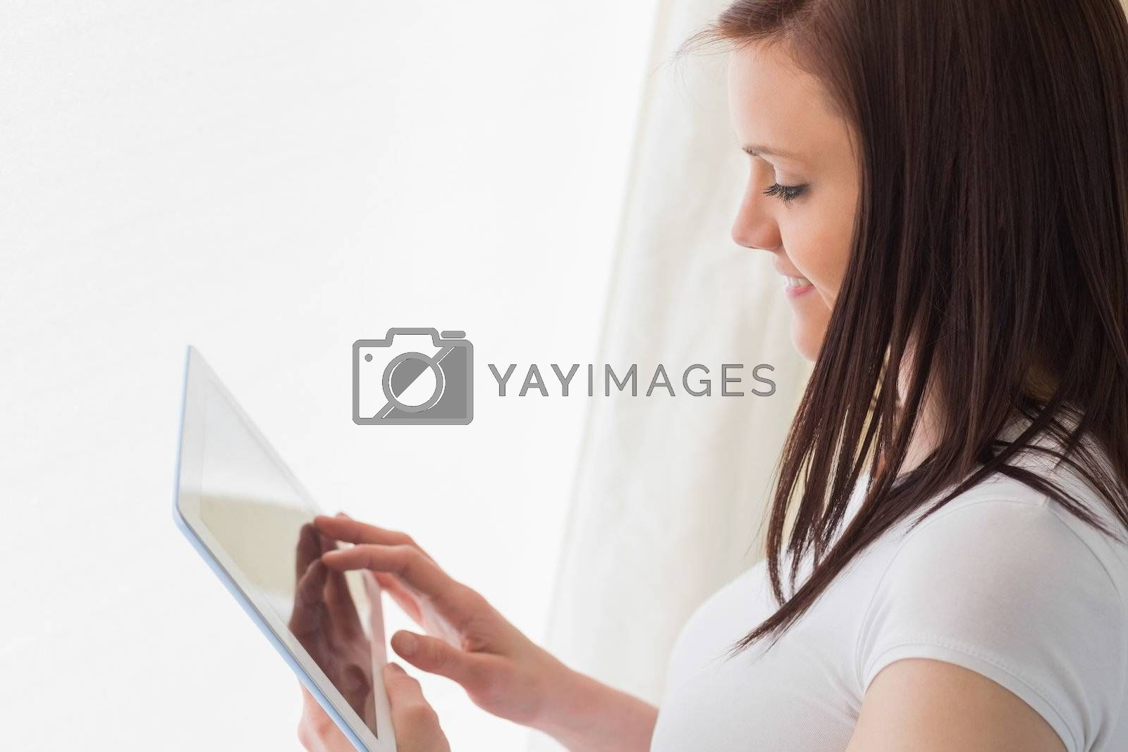 Smiling girl using a tablet pc  by Wavebreakmedia