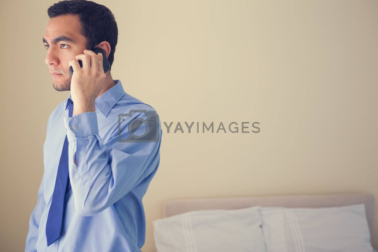 Bored man calling someone withmobile phone and looking away by Wavebreakmedia
