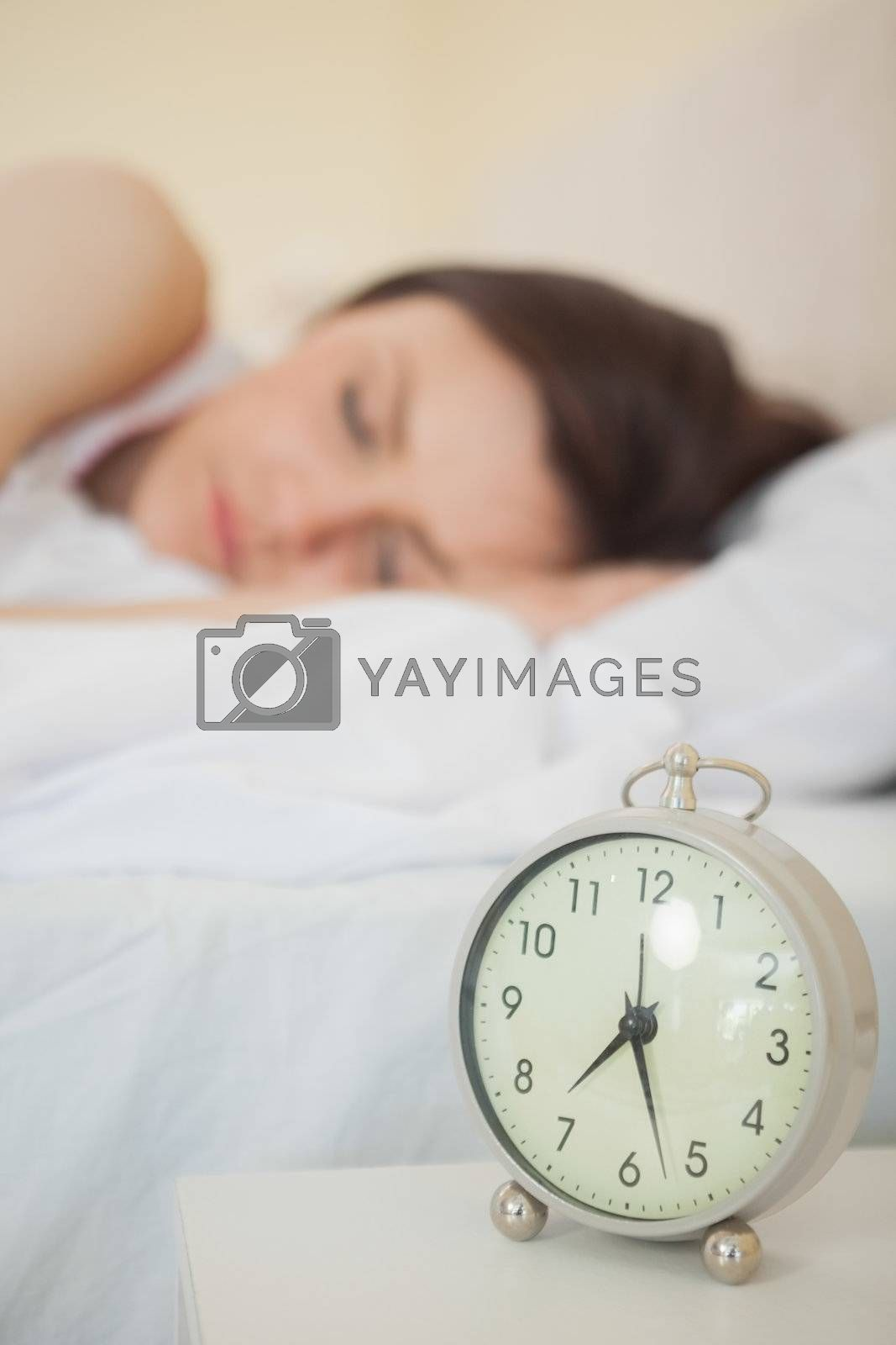 Girl sleeping in her bed with an alarm clock on foreground by Wavebreakmedia
