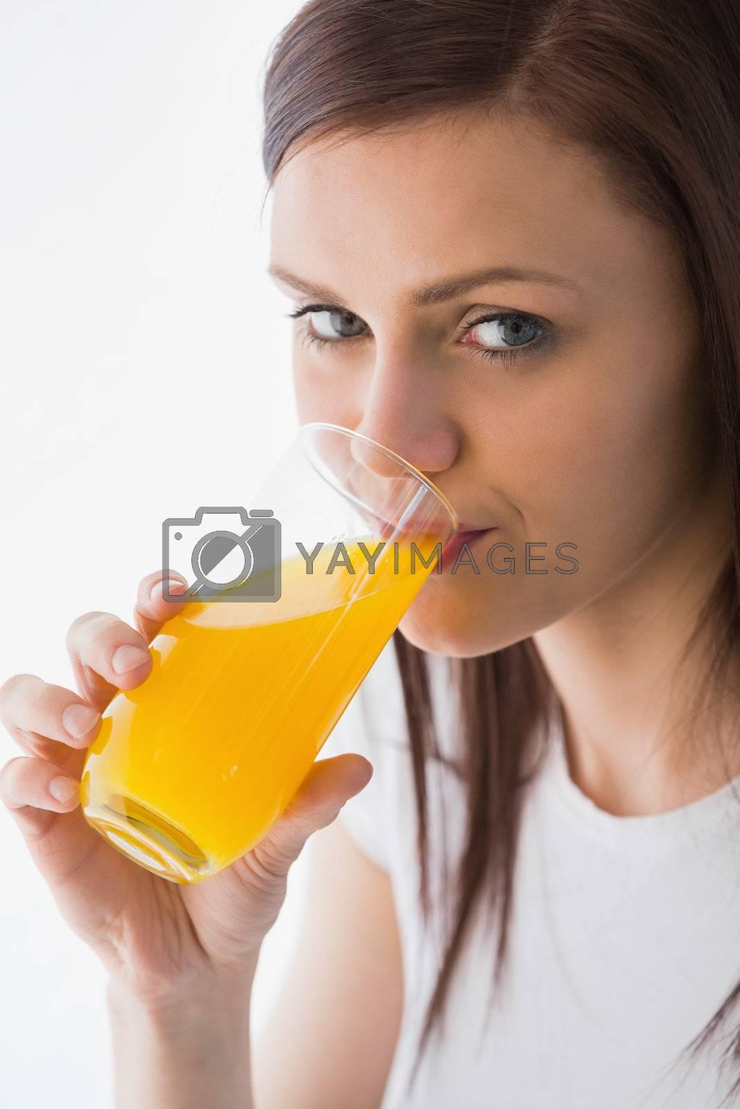 Smiling girl drinking a glass of orange juice by Wavebreakmedia