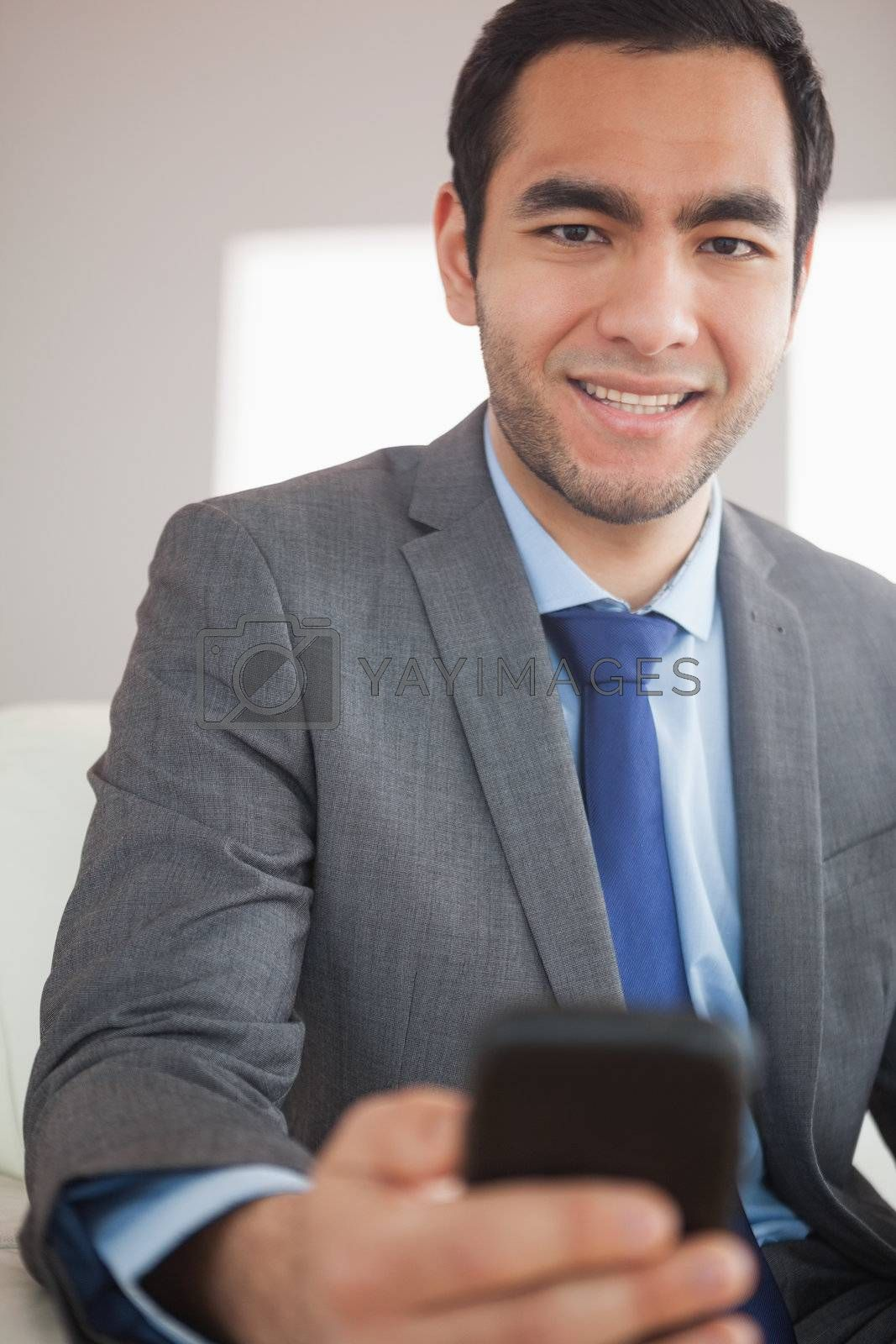 Smiling businessman sending a text message by Wavebreakmedia