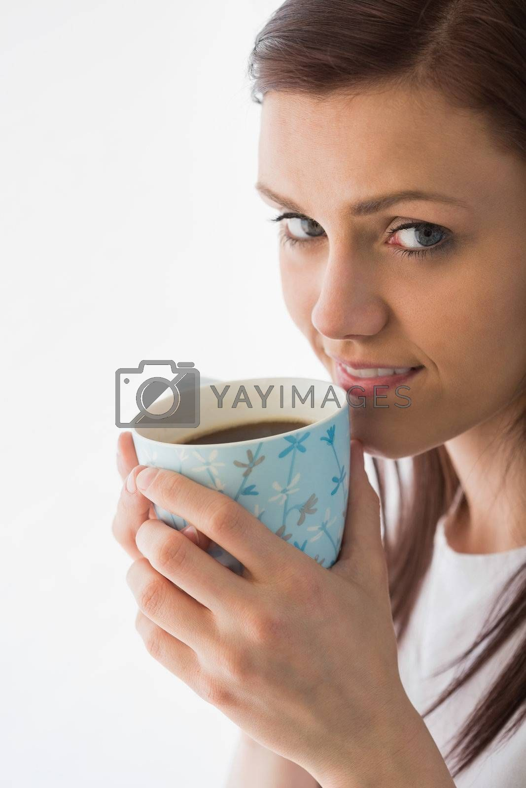 Thoughtful girl looking at camera and drinking a cup of coffee  by Wavebreakmedia
