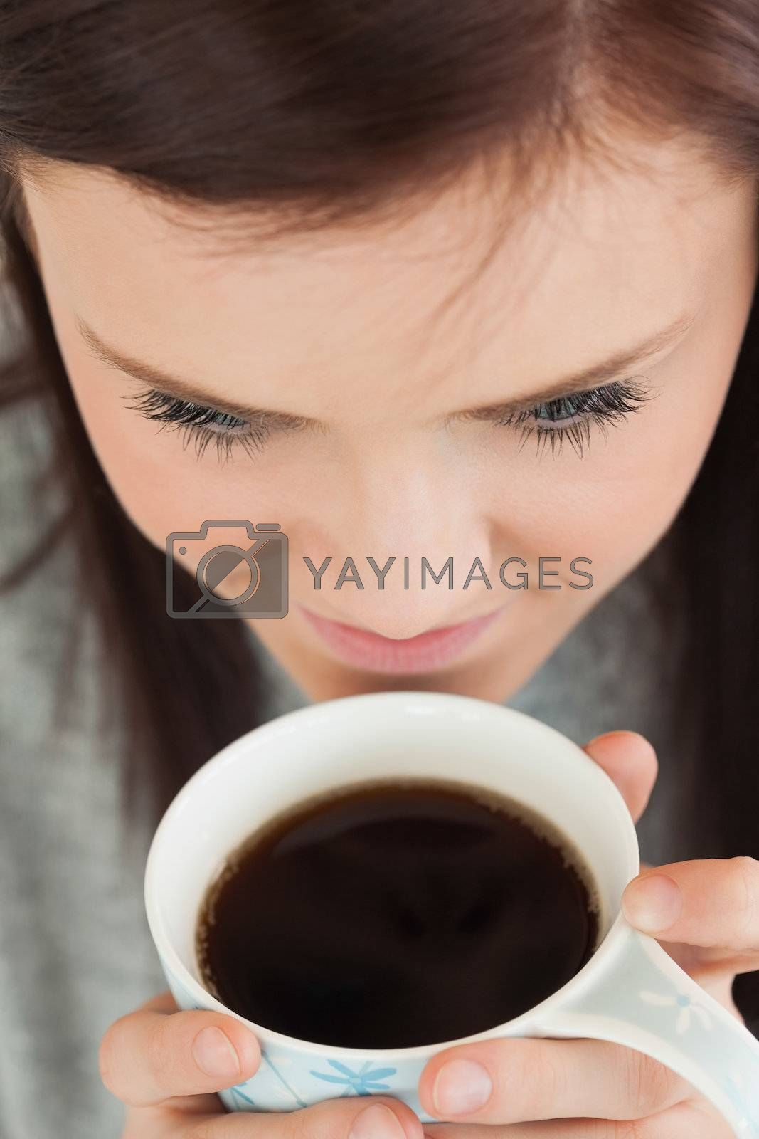 Girl drinking a cup of coffee by Wavebreakmedia