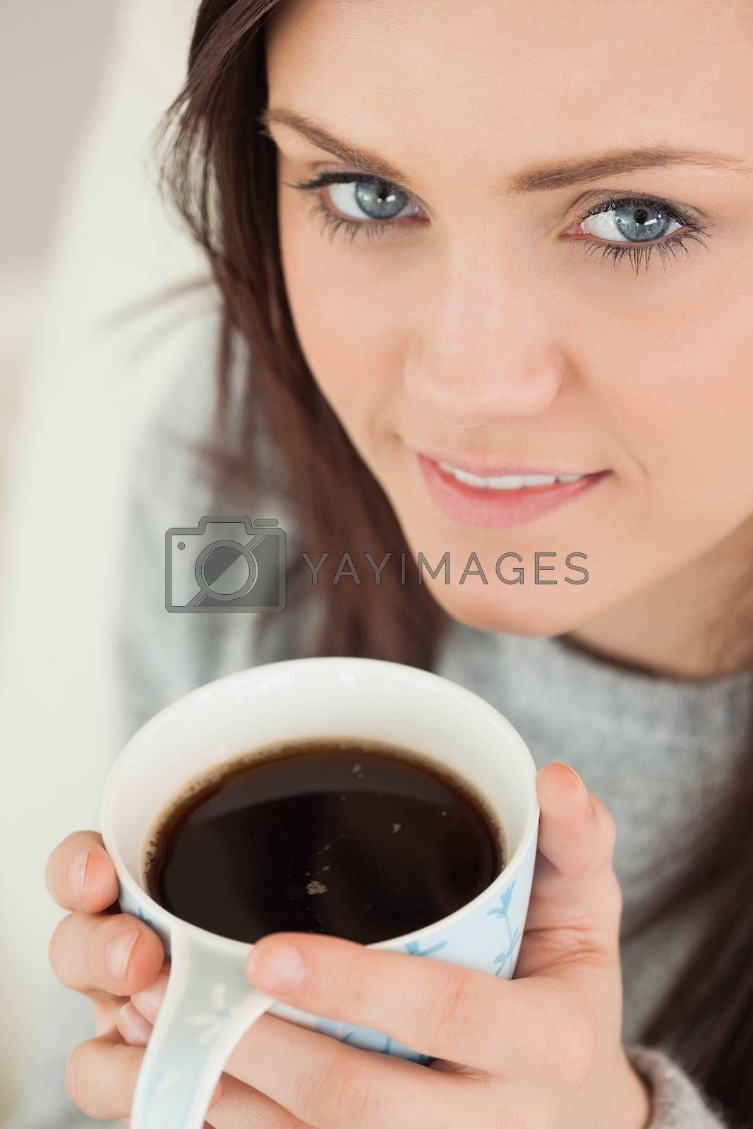 Happy girl holding a cup of coffee by Wavebreakmedia
