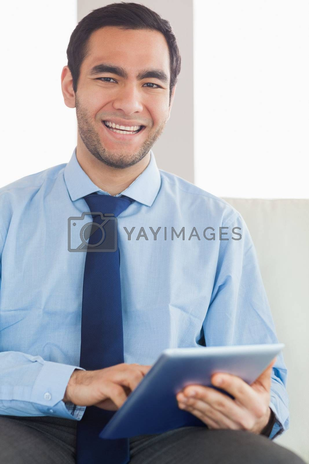 Smiling classy businessman using tablet pc by Wavebreakmedia