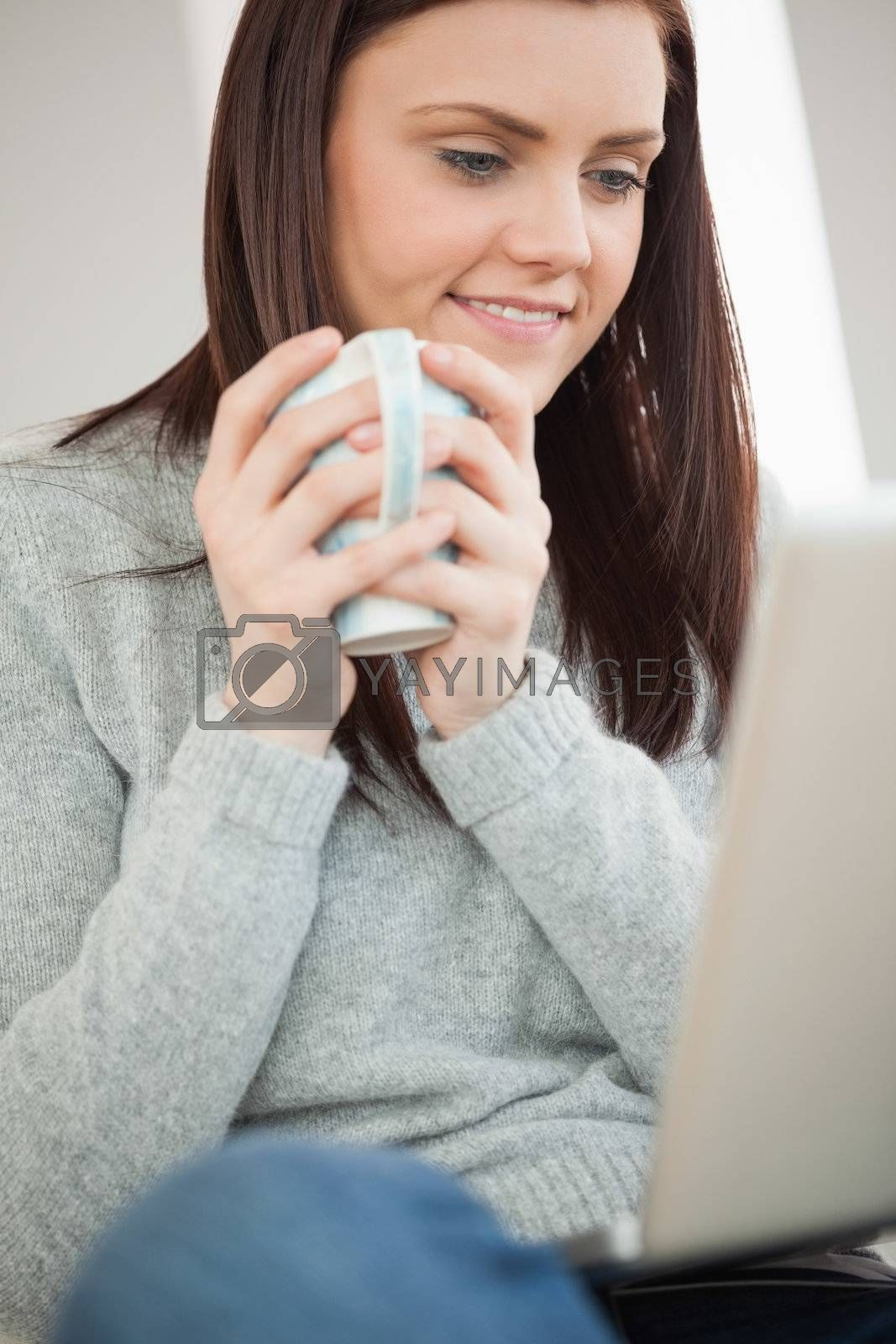 Smiling girl sitting on a sofa holding a cup of coffee and looking at laptop by Wavebreakmedia