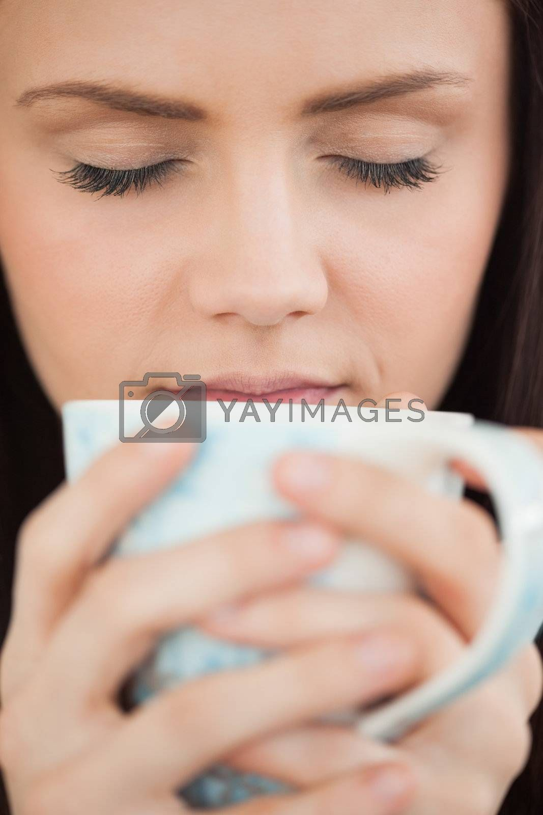 Girl holding a cup of coffee by Wavebreakmedia