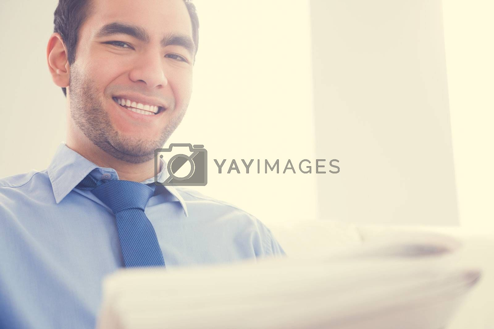 Laughing man looking at camera and reading a newspaper by Wavebreakmedia