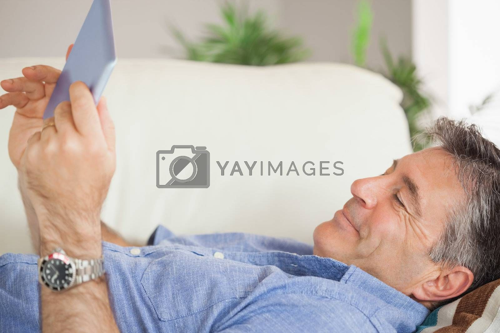 Smiling man laying on a sofa using a tablet pc by Wavebreakmedia