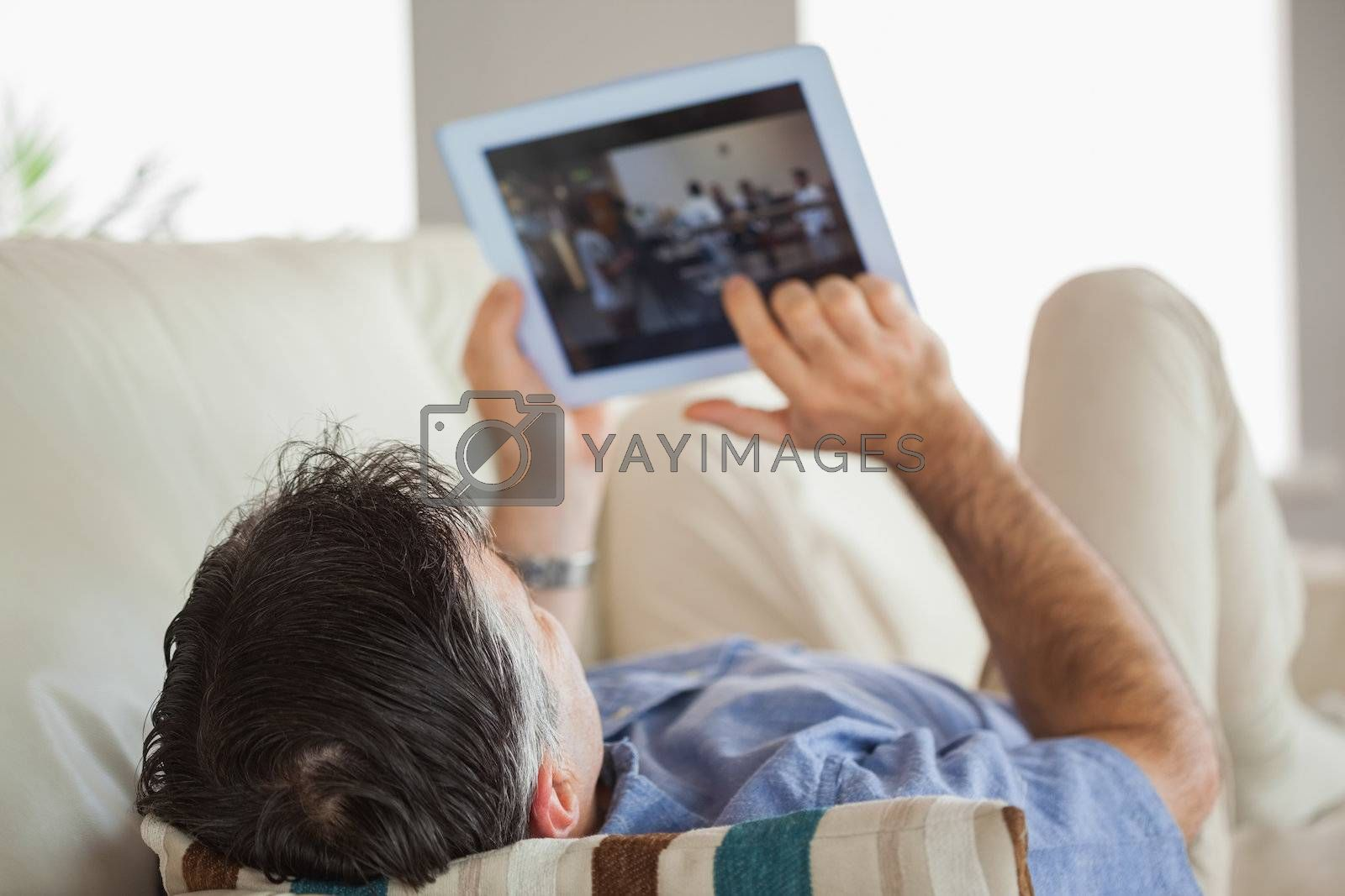 Man laying on a sofa using a tablet pc  by Wavebreakmedia
