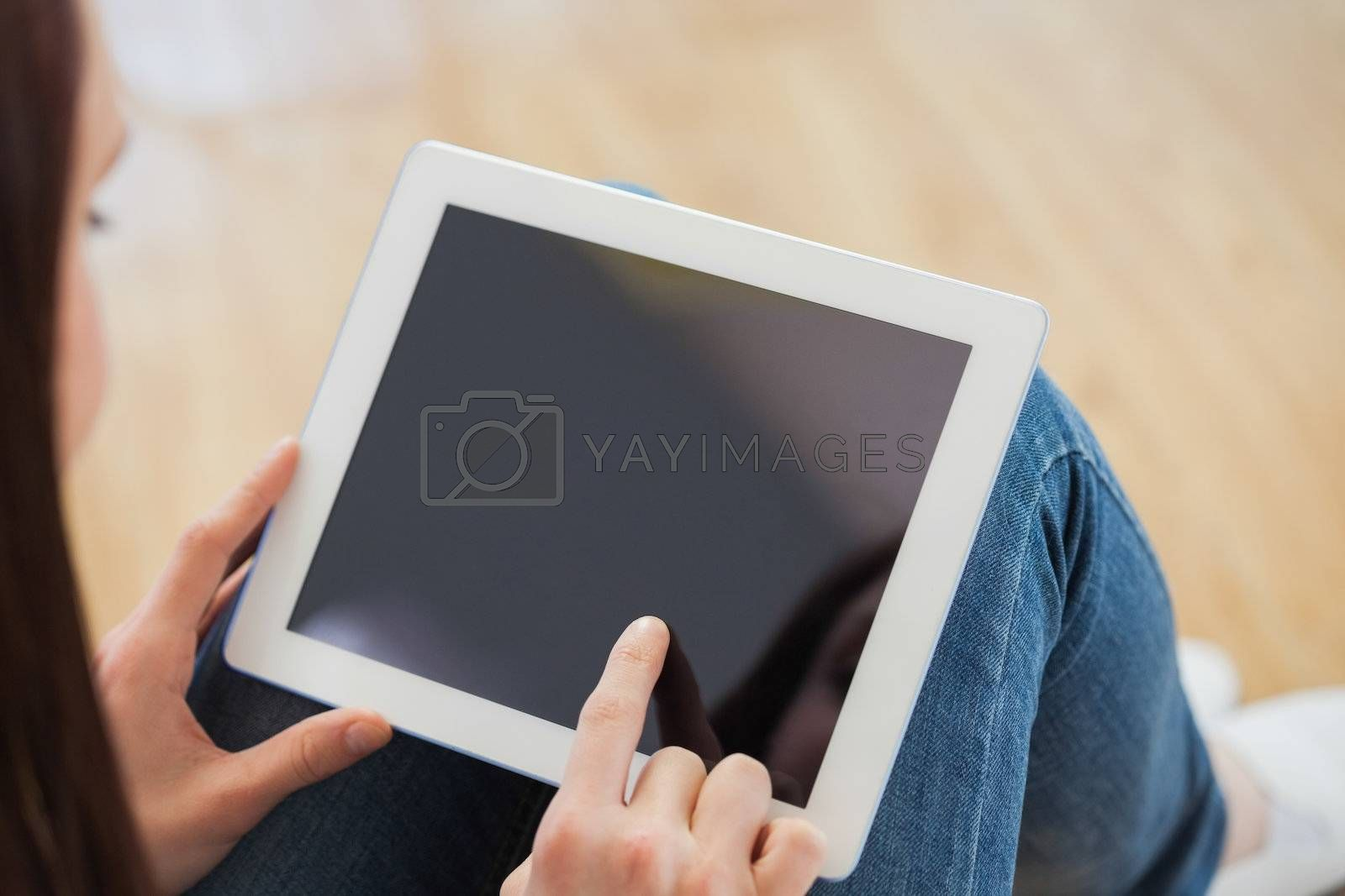 Teen using a tablet pc sitting on the floor by Wavebreakmedia