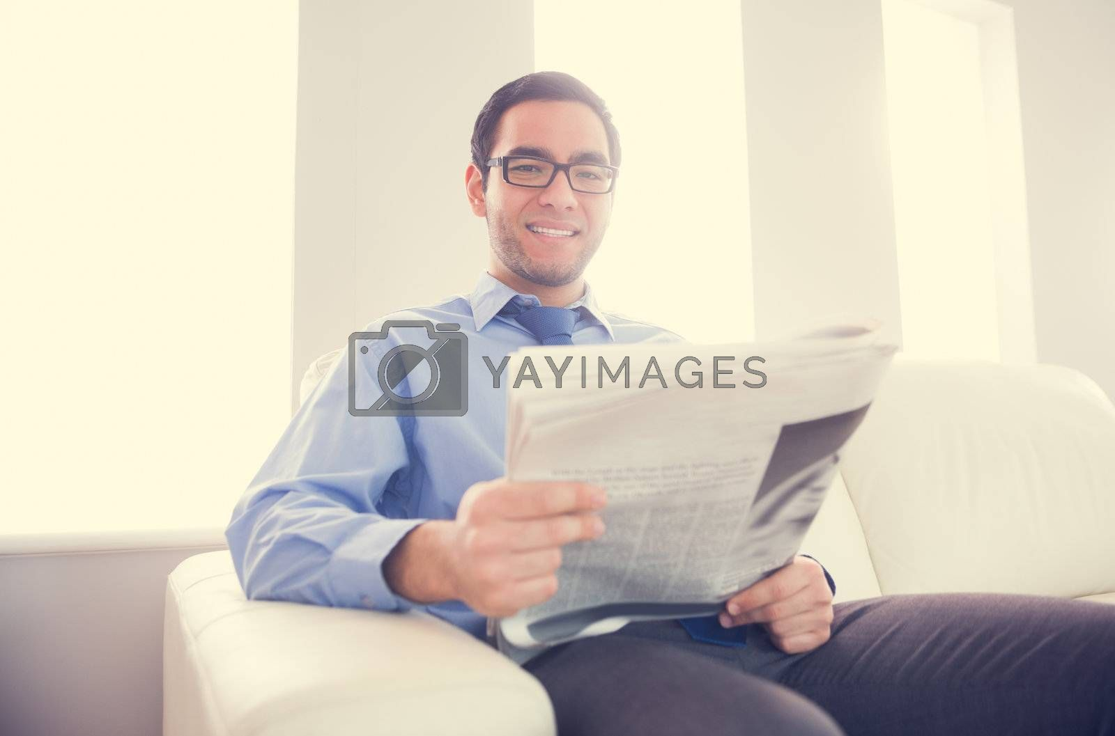 Pleased man looking at camera and holding a newspaper sitting on a sofa by Wavebreakmedia