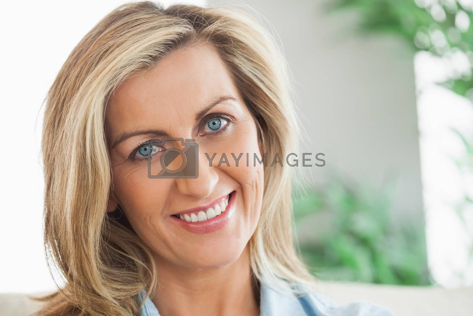 Woman smiling and looking at camera by Wavebreakmedia