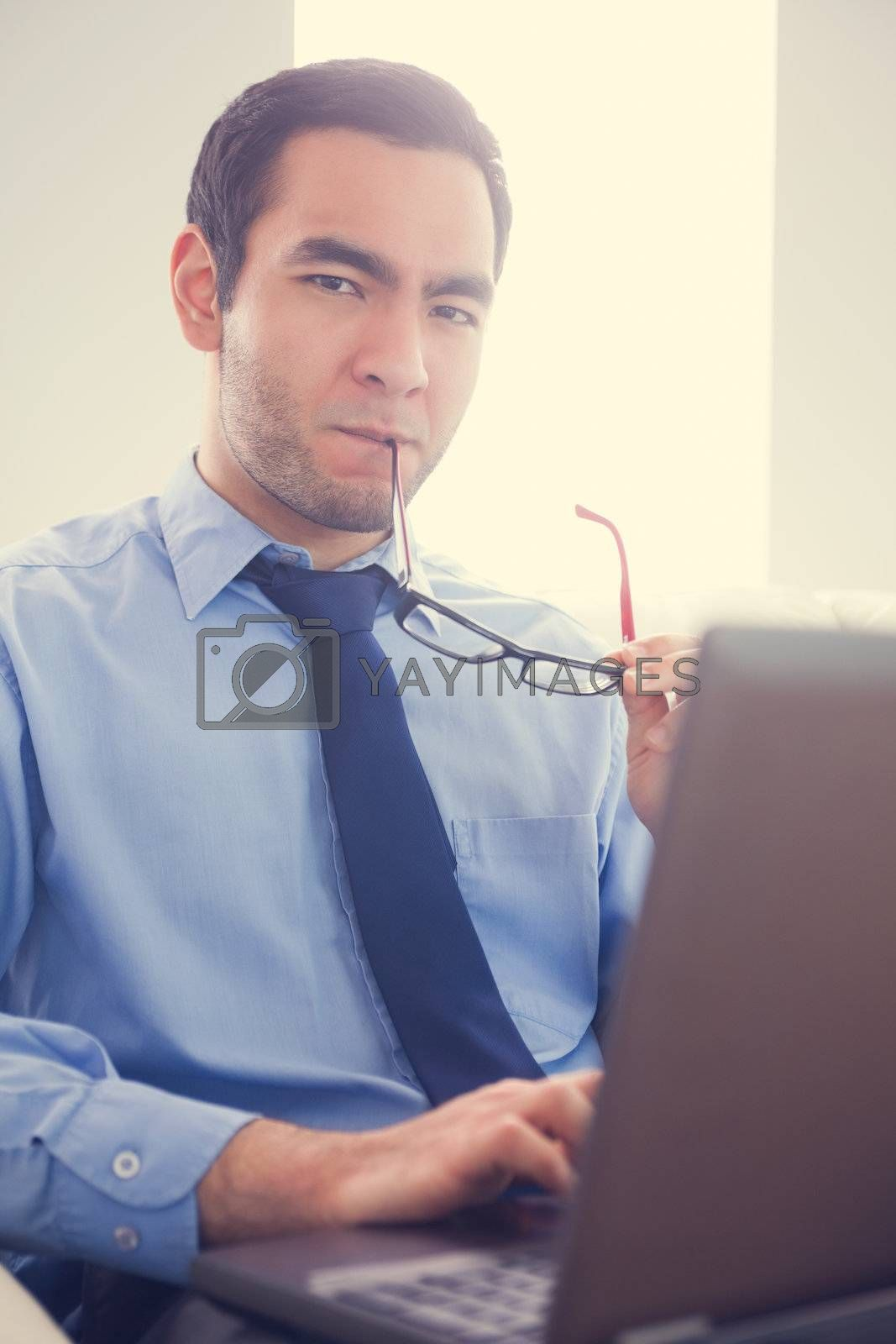 Irritated man biting his eyeglasses and using a laptop by Wavebreakmedia